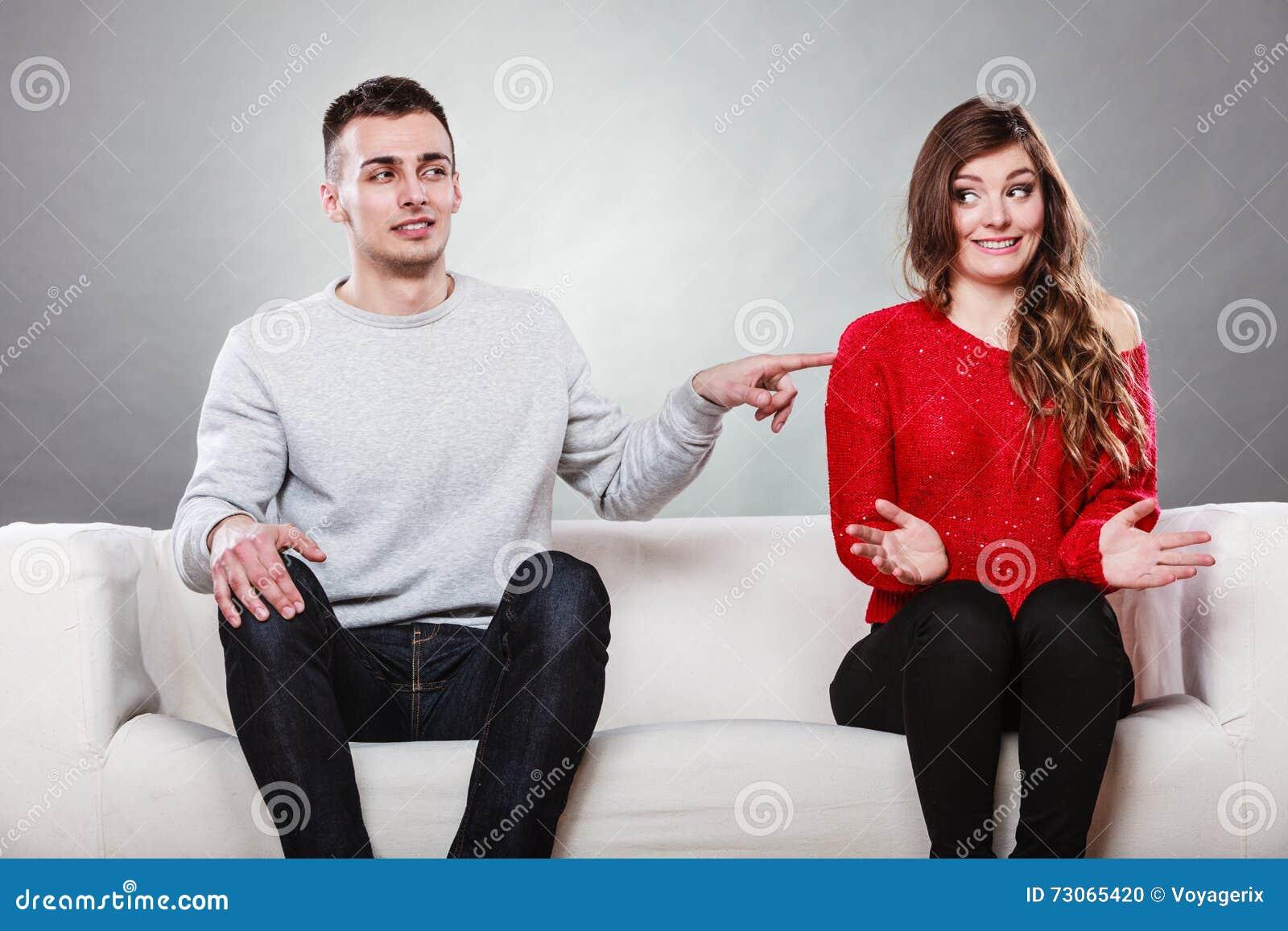 Mulher tímida e homem que sentam-se no sofá Primeira data