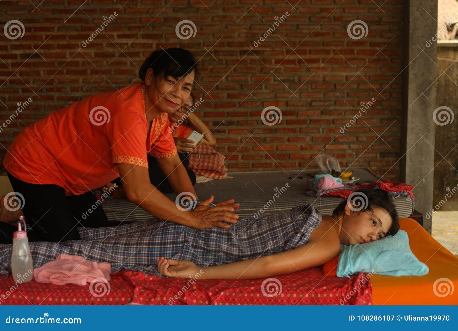 Mulher tailandesa asiática que executa a massagem ao menino europeu do adolescente