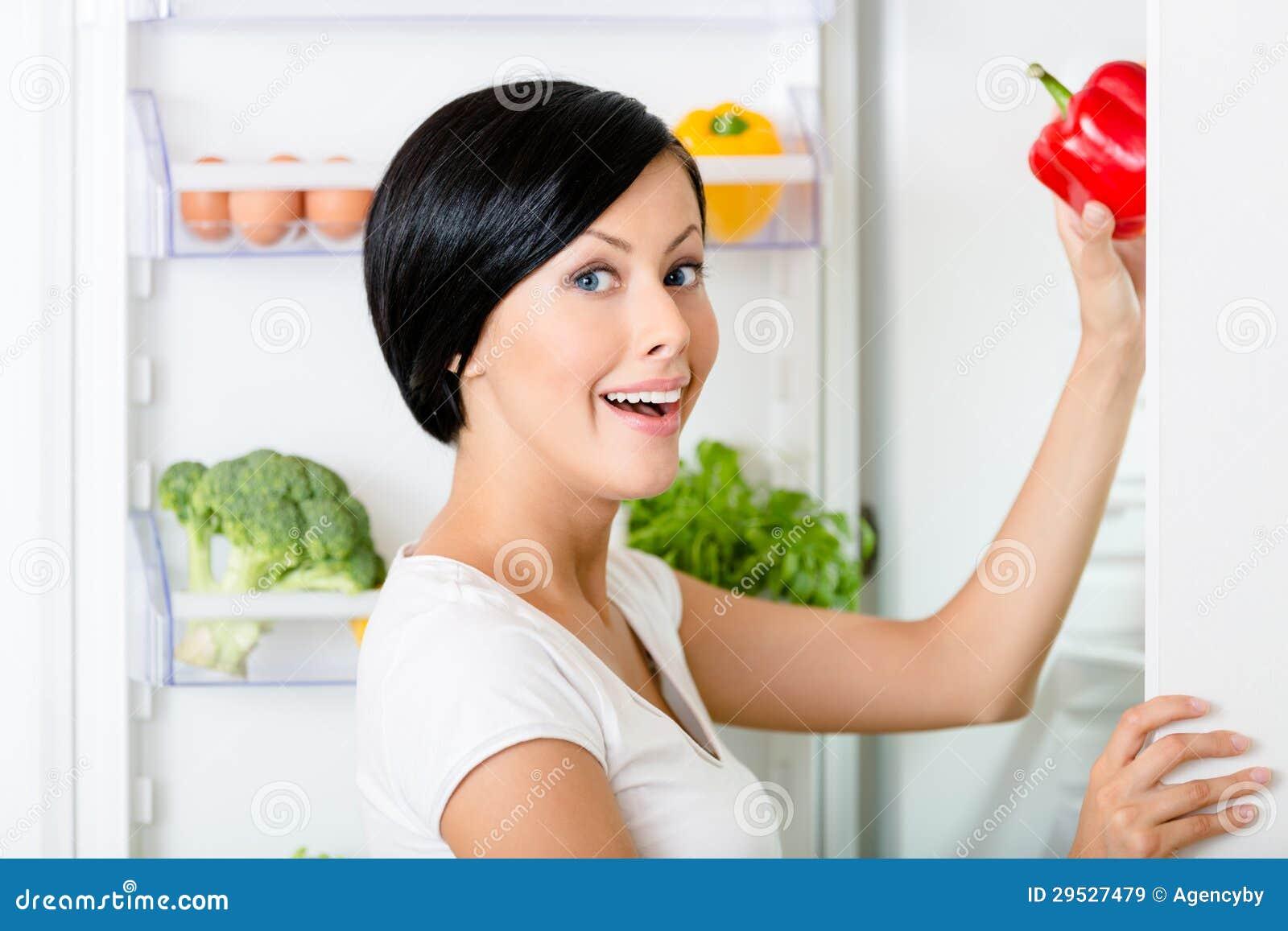 A mulher toma a pimenta vermelha do refrigerador aberto