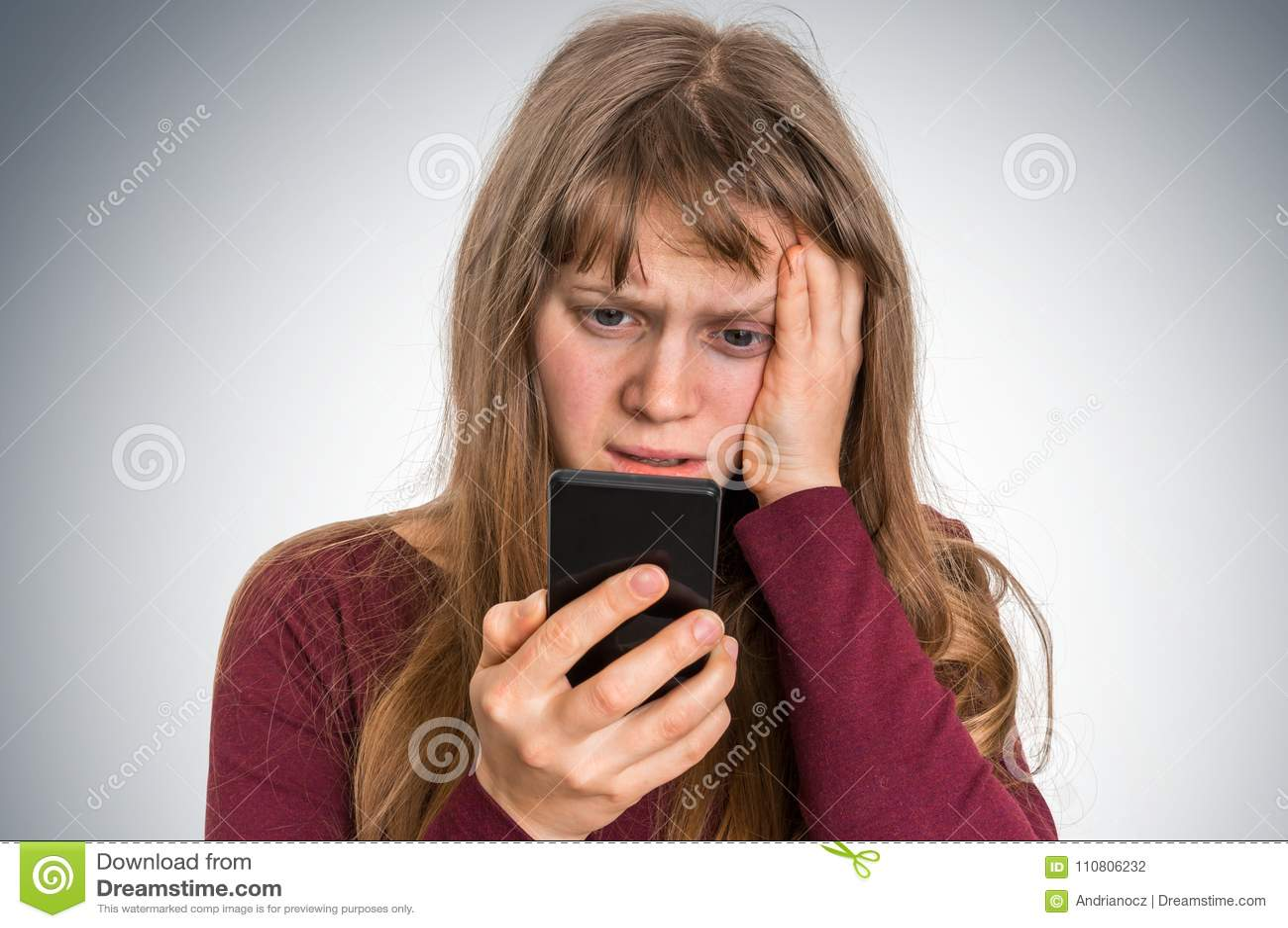 Mulher triste com telefone celular - conceito das más notícias