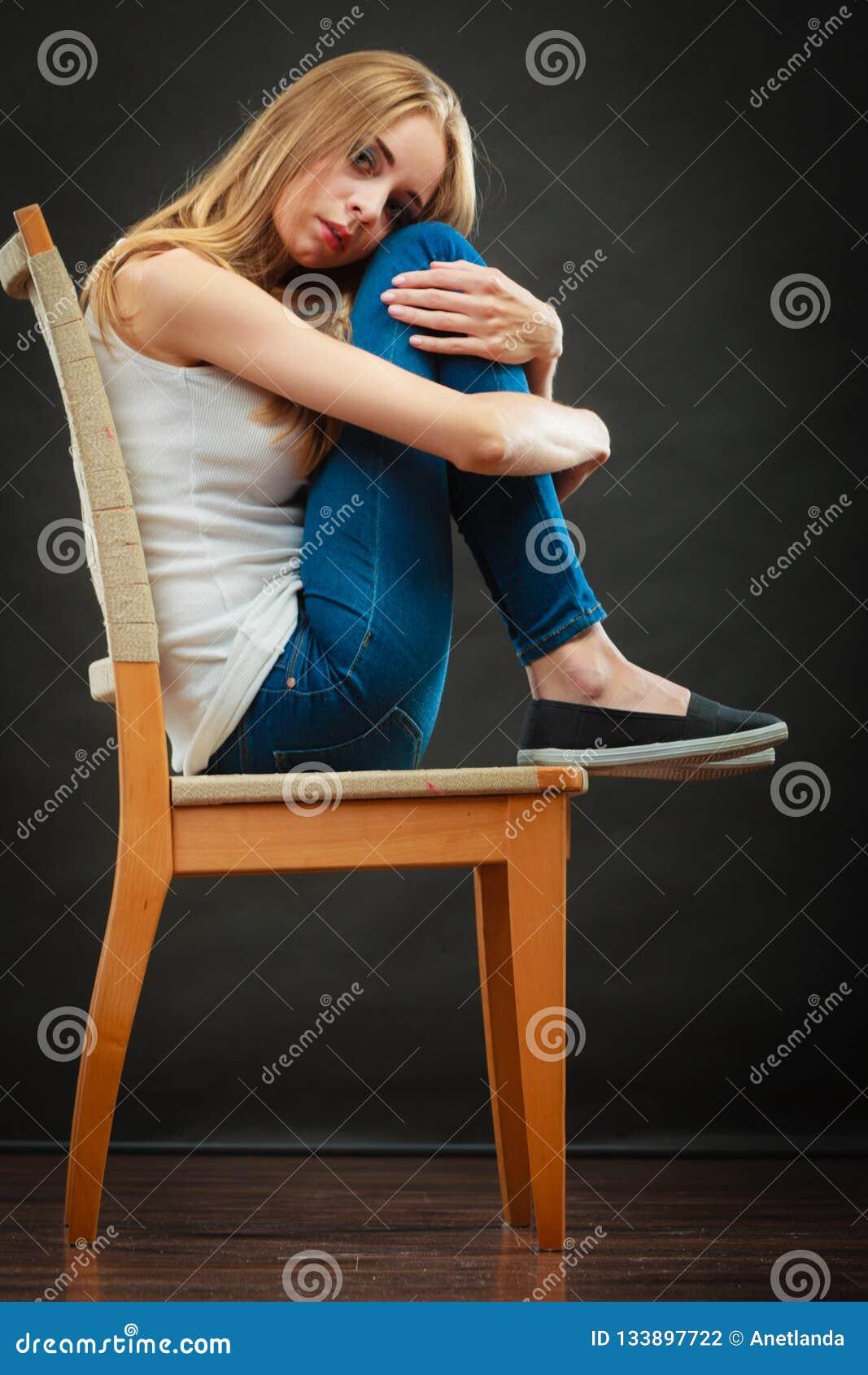 Mulher triste nova que senta-se na cadeira