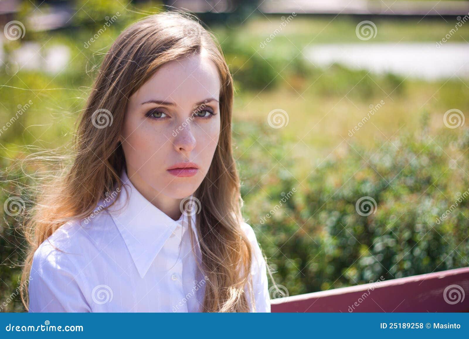 A mulher triste olha na câmera