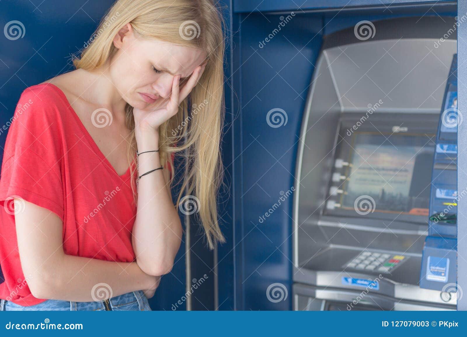 Mulher triste que está na frente de uma máquina do banco do ATM Nenhum dinheiro