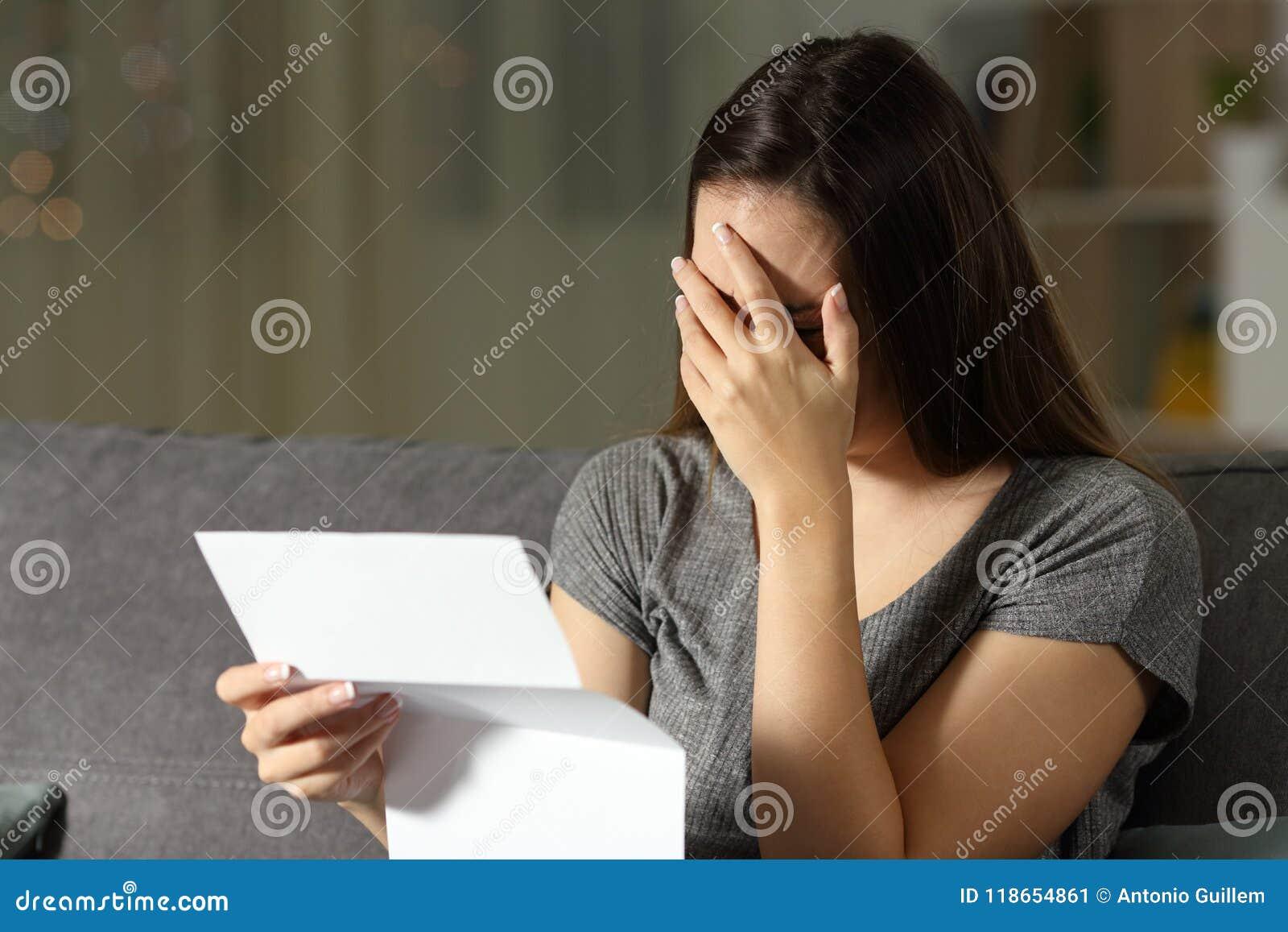 Mulher triste que lê uma letra na obscuridade