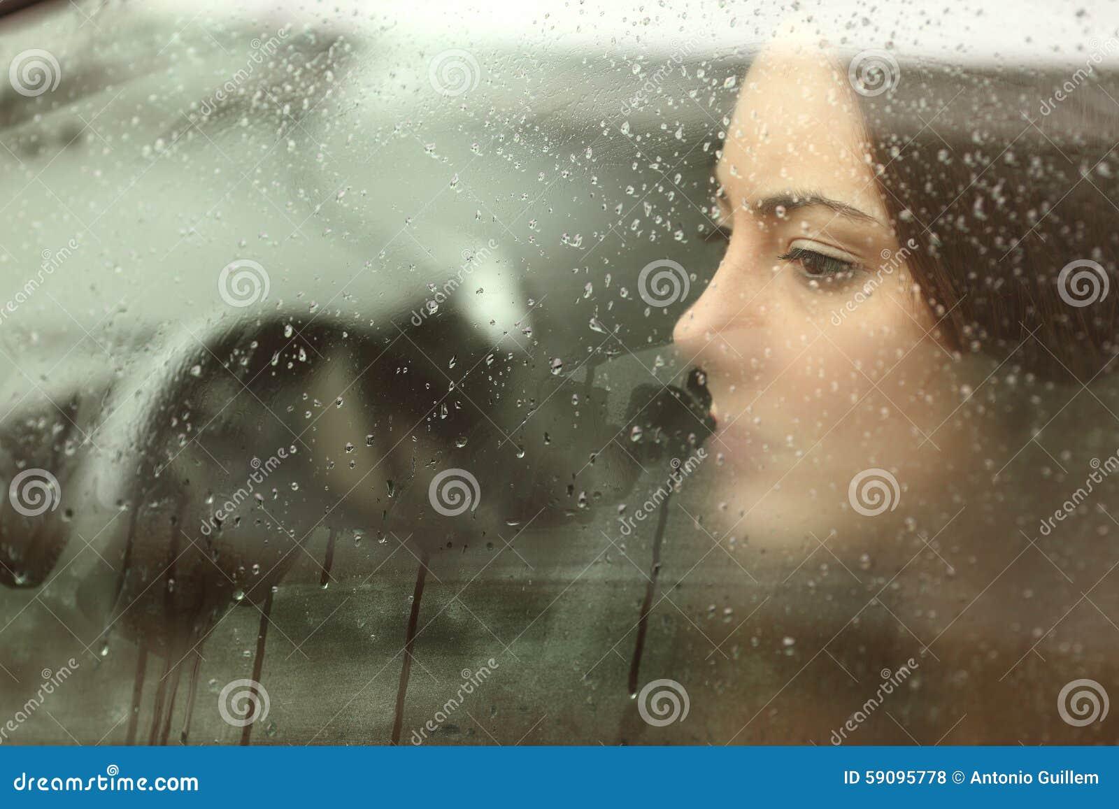 Mulher triste que olha através de uma janela de carro