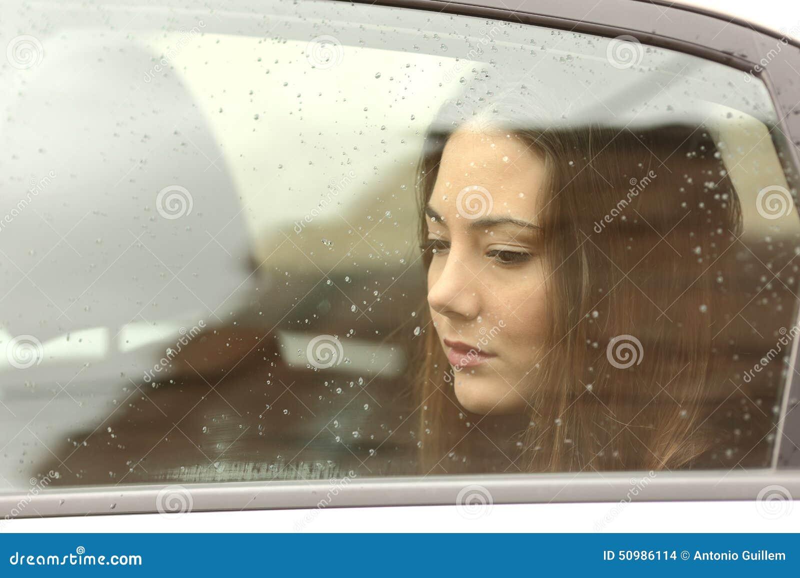 Mulher triste que olha para baixo através de uma janela de carro