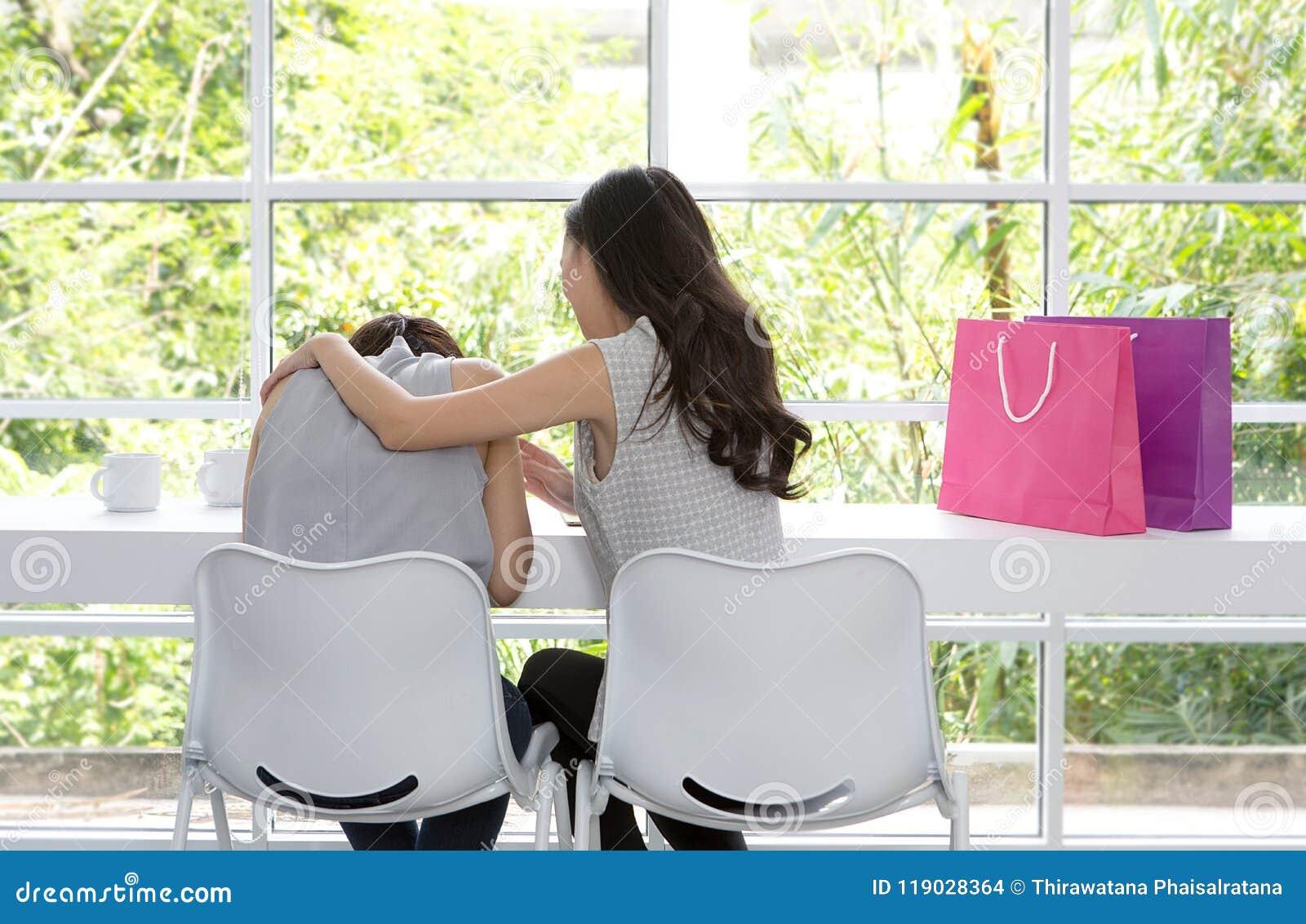 Mulher triste que senta-se na sala Os amigos não dão acima Menina triste e amigos de apoio para resolver um problema