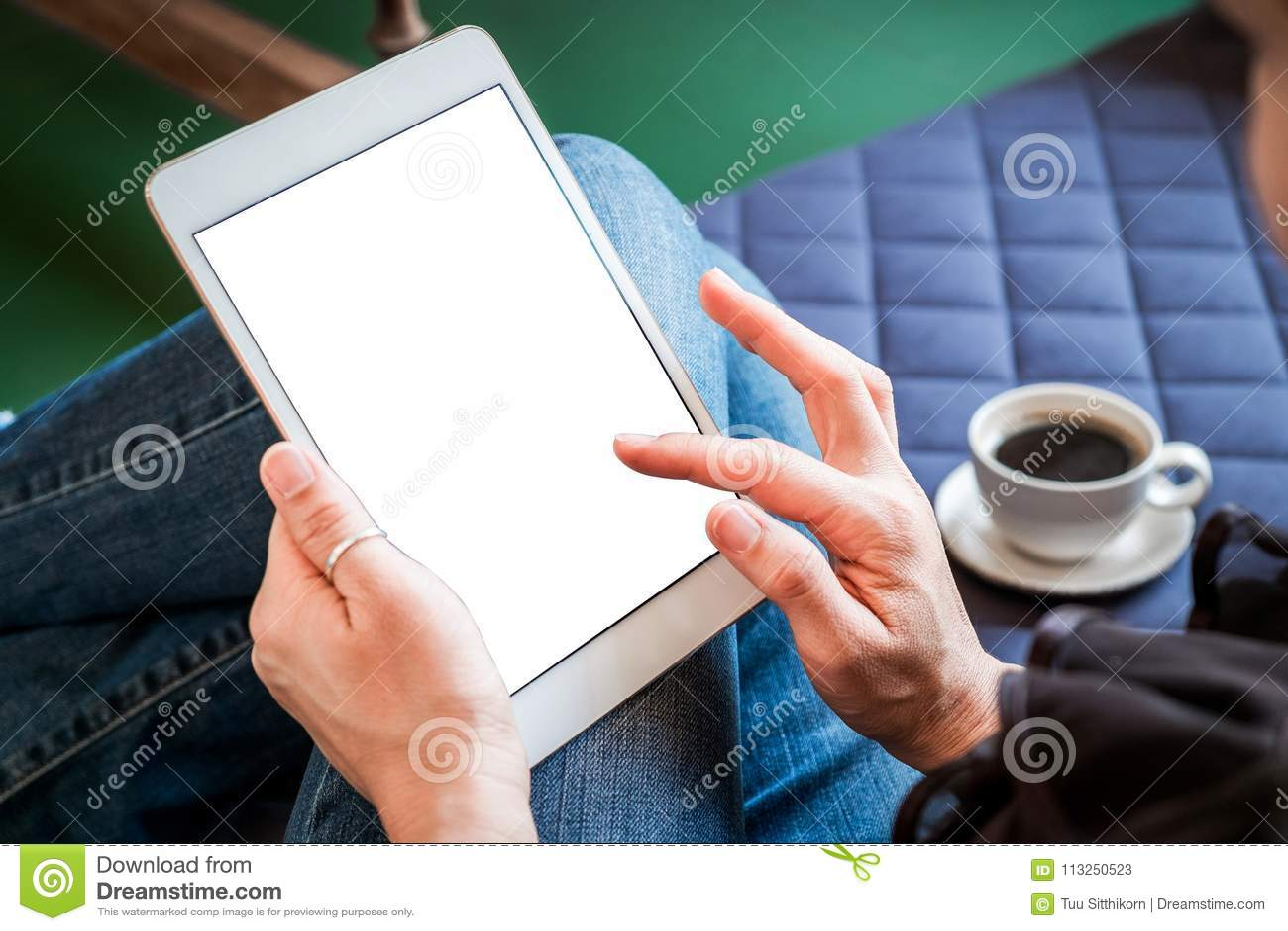 A mulher usa a tabuleta ao relaxar em casa com café no sofá