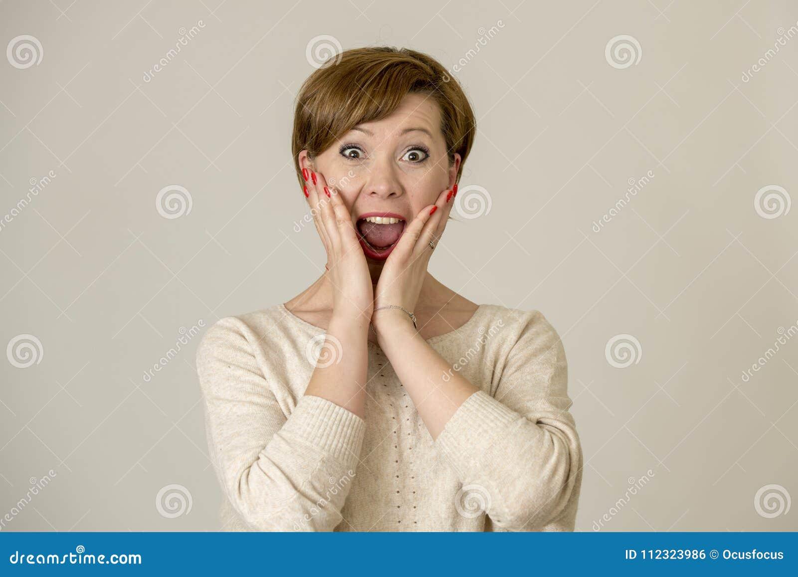 Mulher vermelha feliz e surpreendida nova do cabelo que olha à câmera deleitada surpreendida e na expressão da cara da surpresa i
