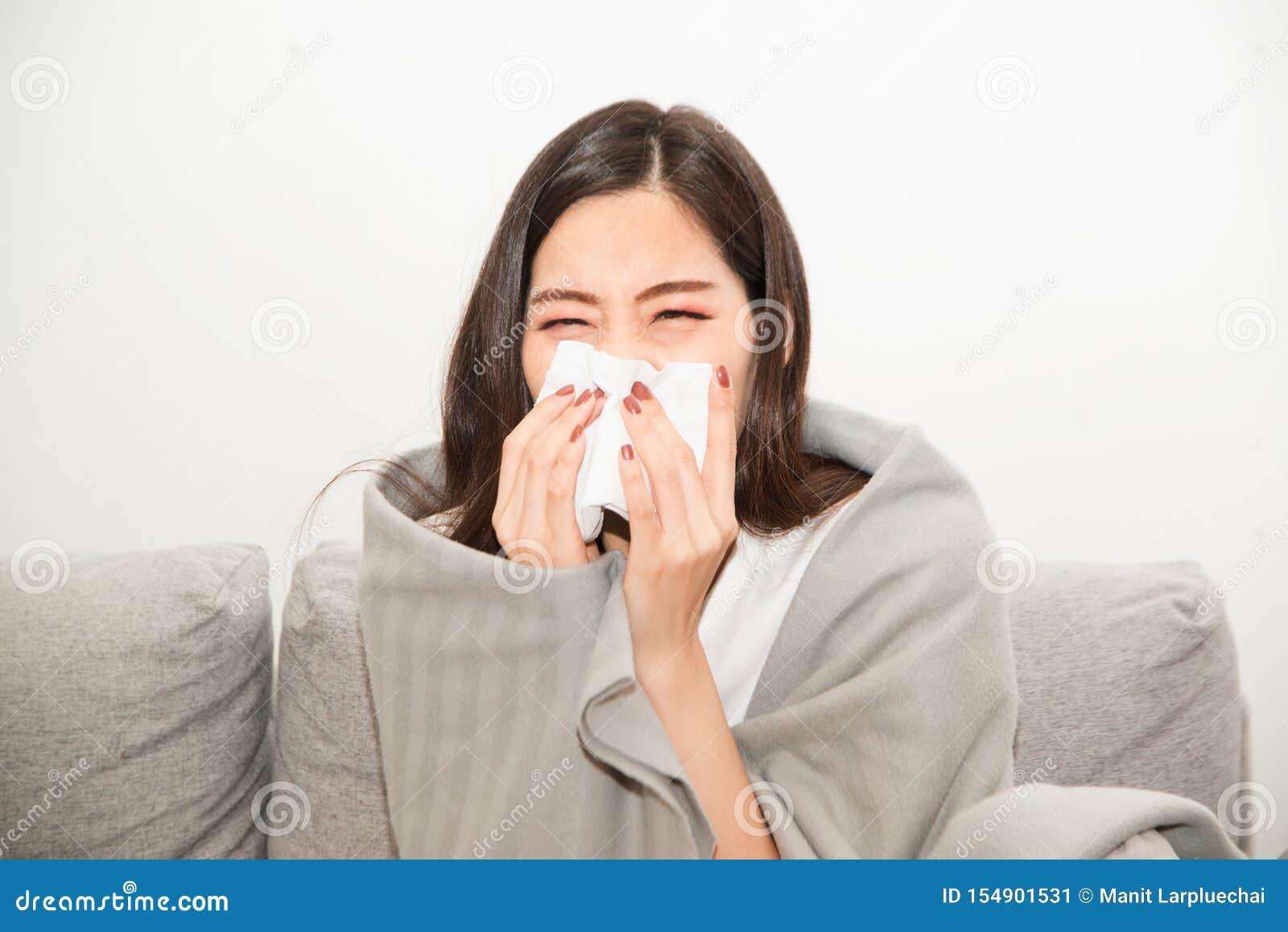 Mulheres asiáticas com esforço que sofrem das alergias e fecham o nariz com lenço de papel Devido a ter espirrar todo o tempo
