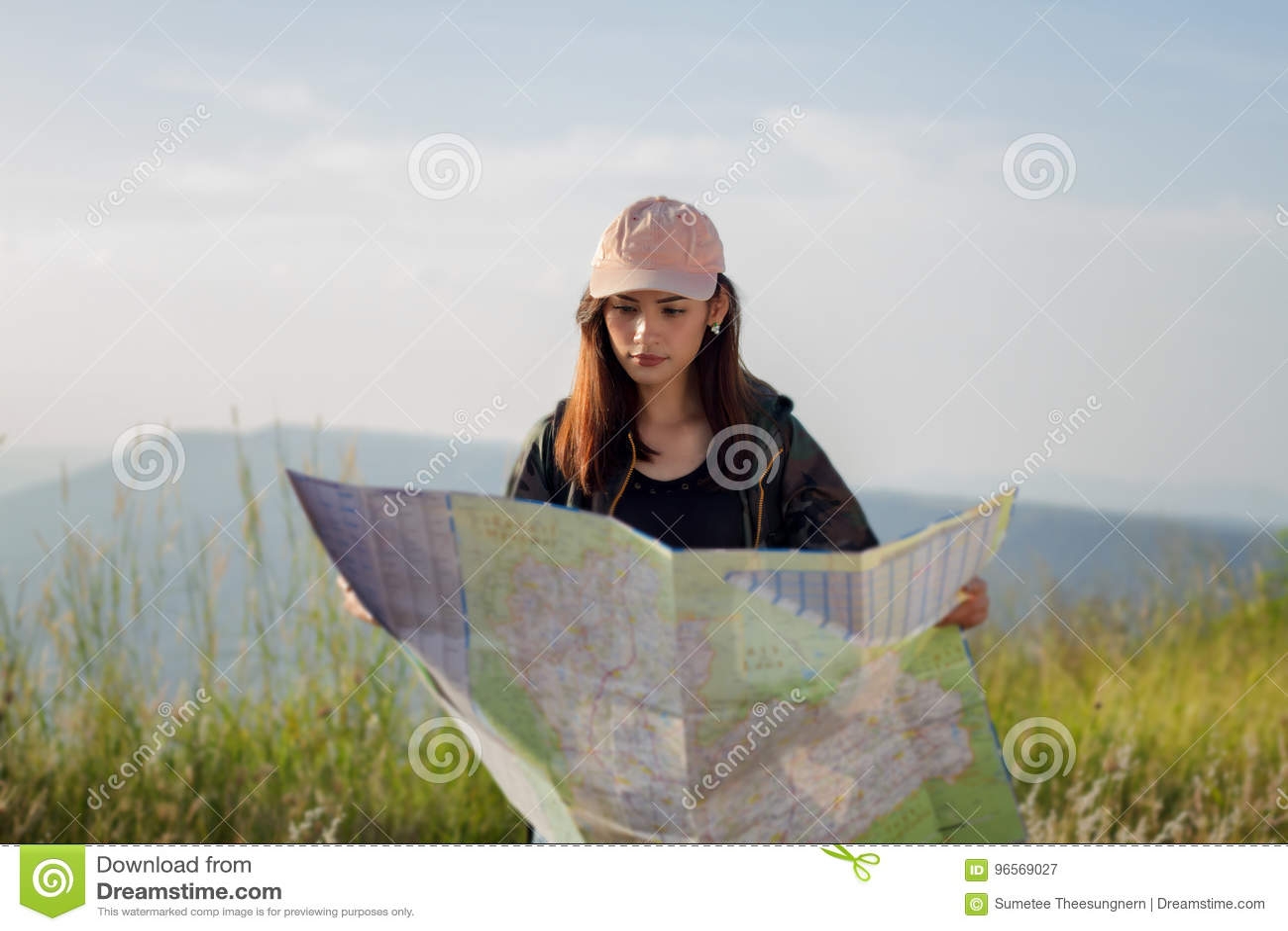 Mulheres asiáticas com a trouxa brilhante que olha um mapa Vista do CCB
