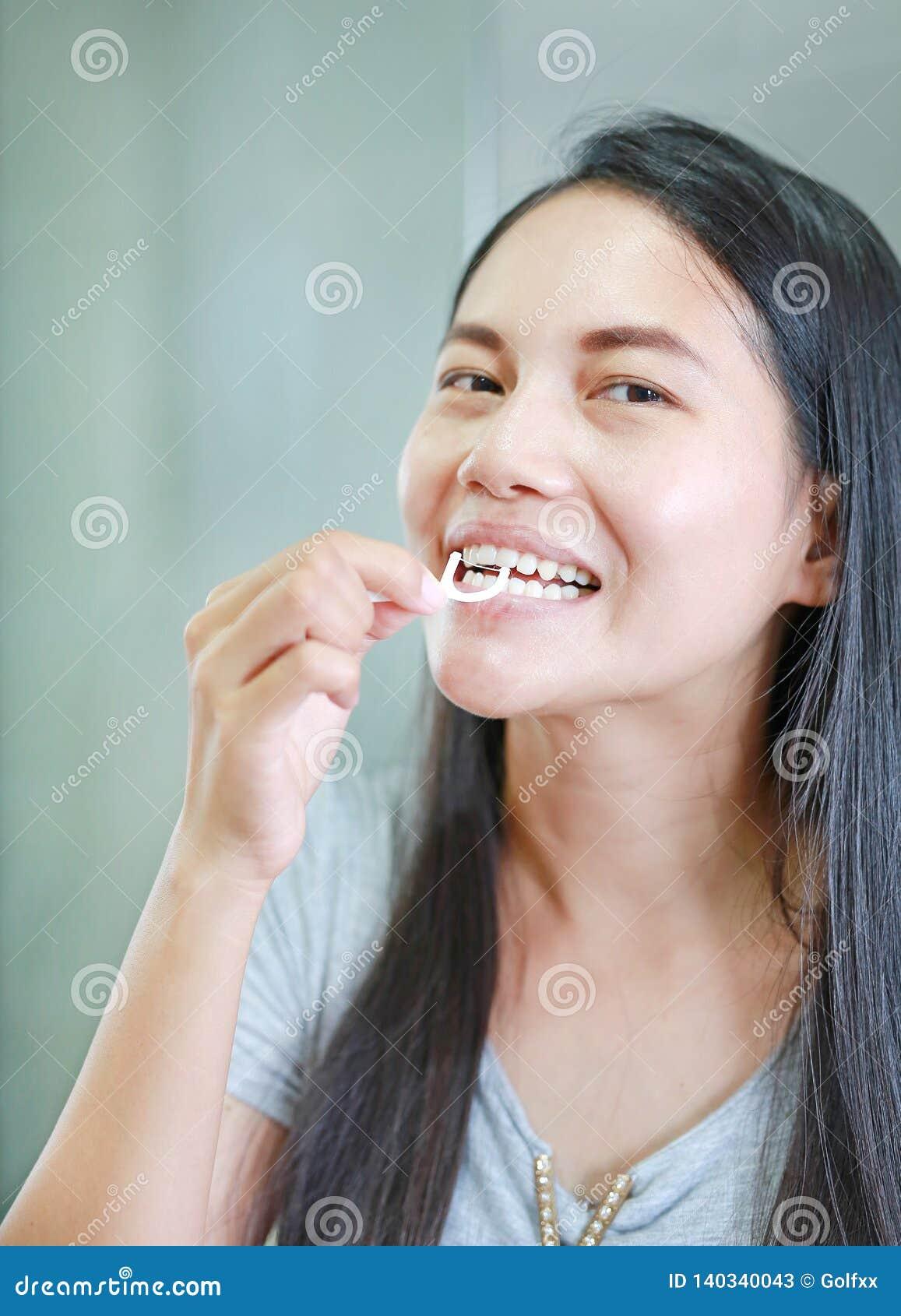 Mulheres asiáticas de sorriso que usam o fio dental para os dentes saudáveis