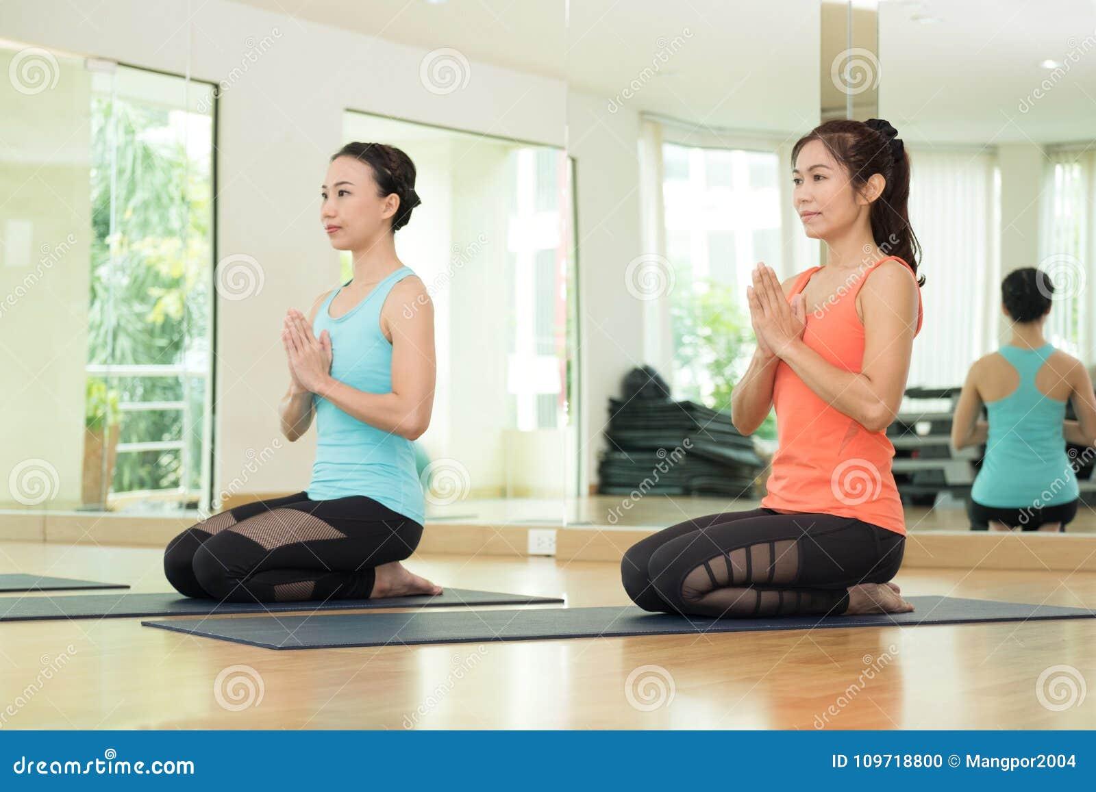 Mulheres asiáticas novas que praticam a ioga, meditação na pose dos lótus, hea