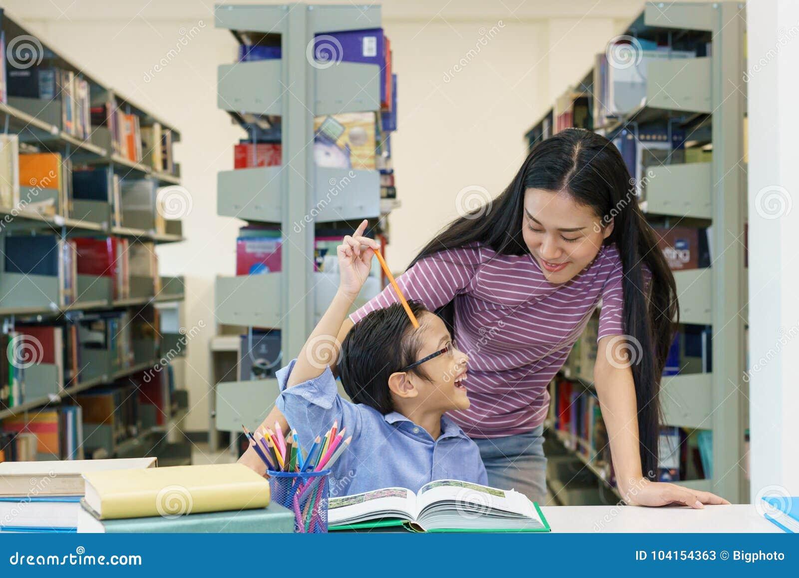 Mulheres bonitas com o livro de leitura do rapaz pequeno junto na biblioteca