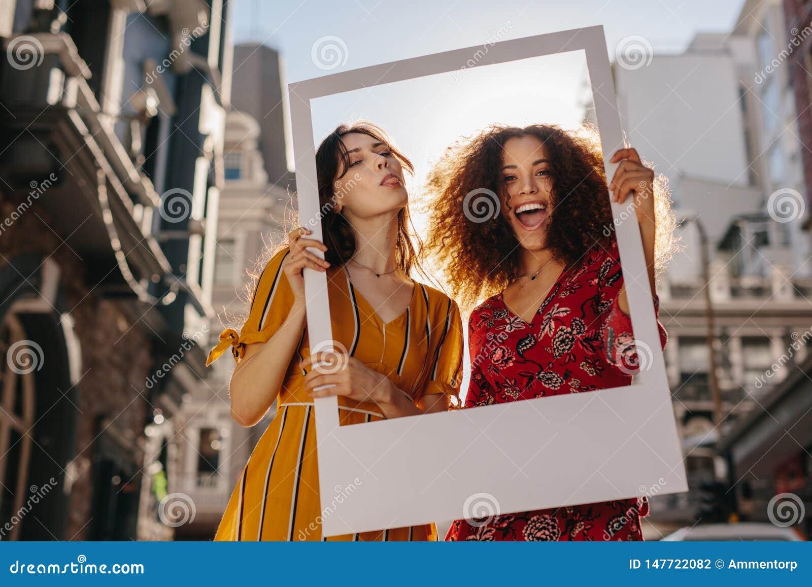 Mulheres bonitas com um quadro vazio da foto