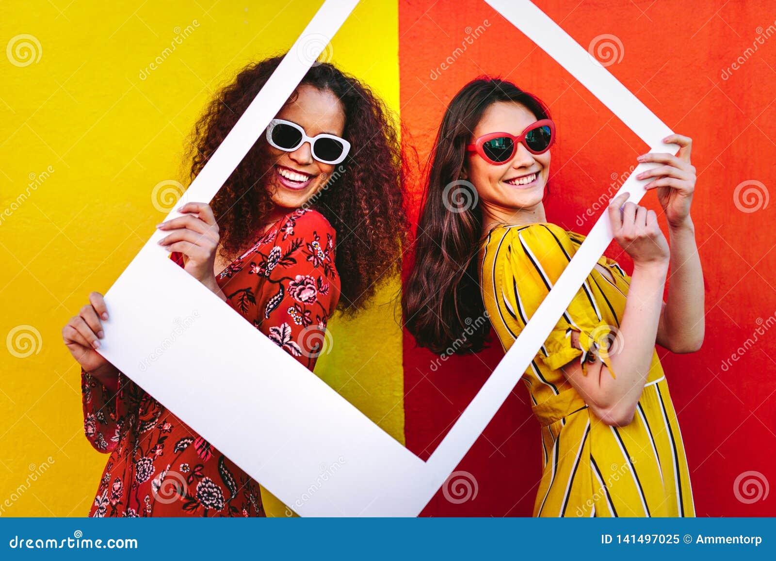 Mulheres bonitas que guardam um quadro vazio da foto