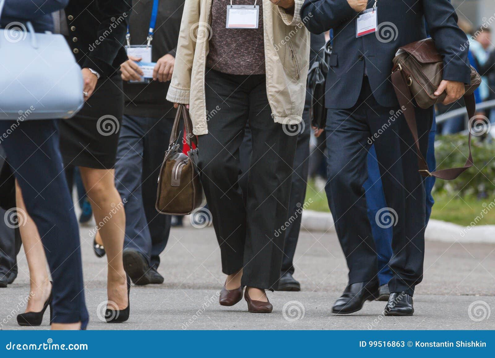 Mulheres de negócios e homens de negócios que andam ao longo da rua na conferência ou na exposição