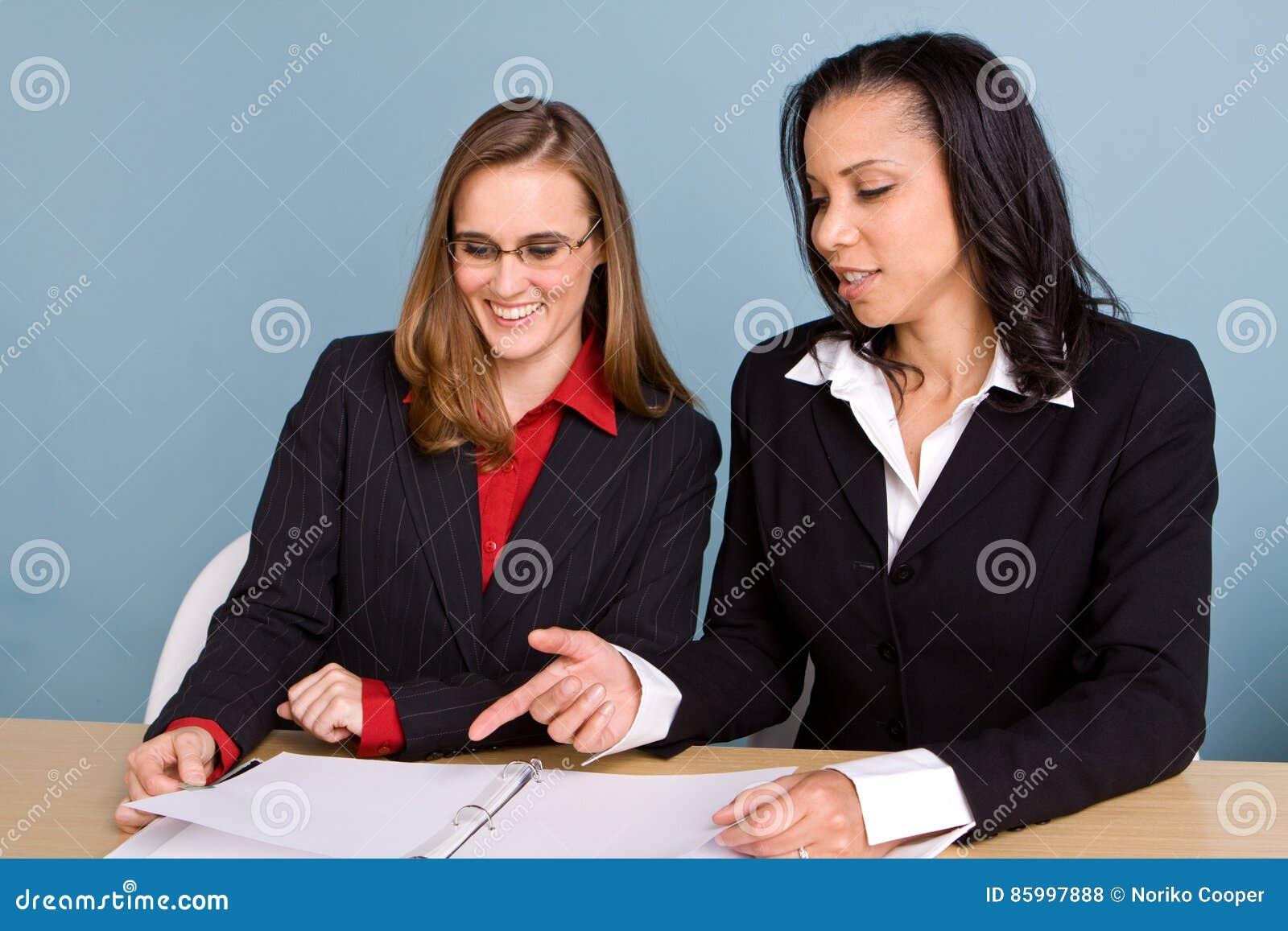 Mulheres de negócios seguras felizes que sorriem no trabalho