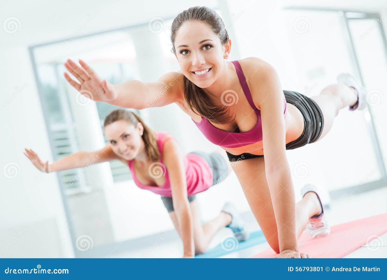 Mulheres desportivas que fazem o exercício dos pilates