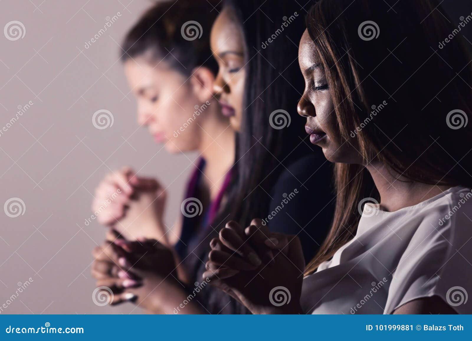 Mulheres devotadas novas que rezam junto