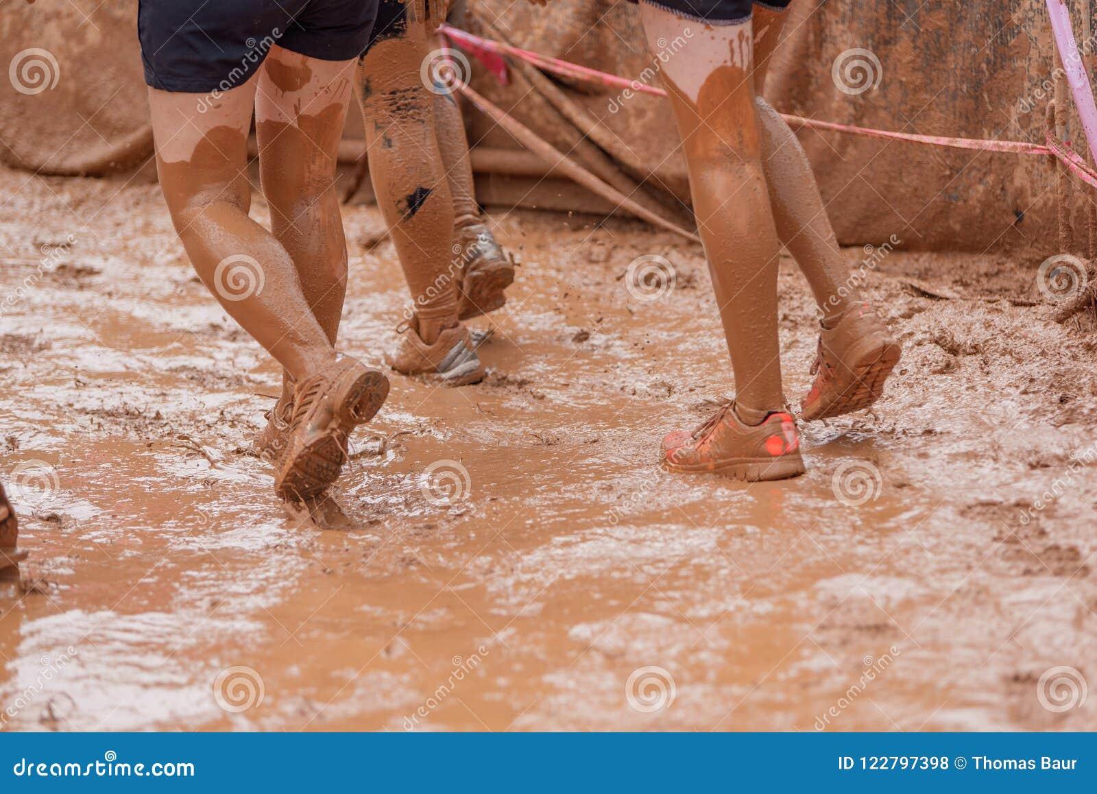 Mulheres do corredor de raça da lama que rastejam na lama sob obstáculos