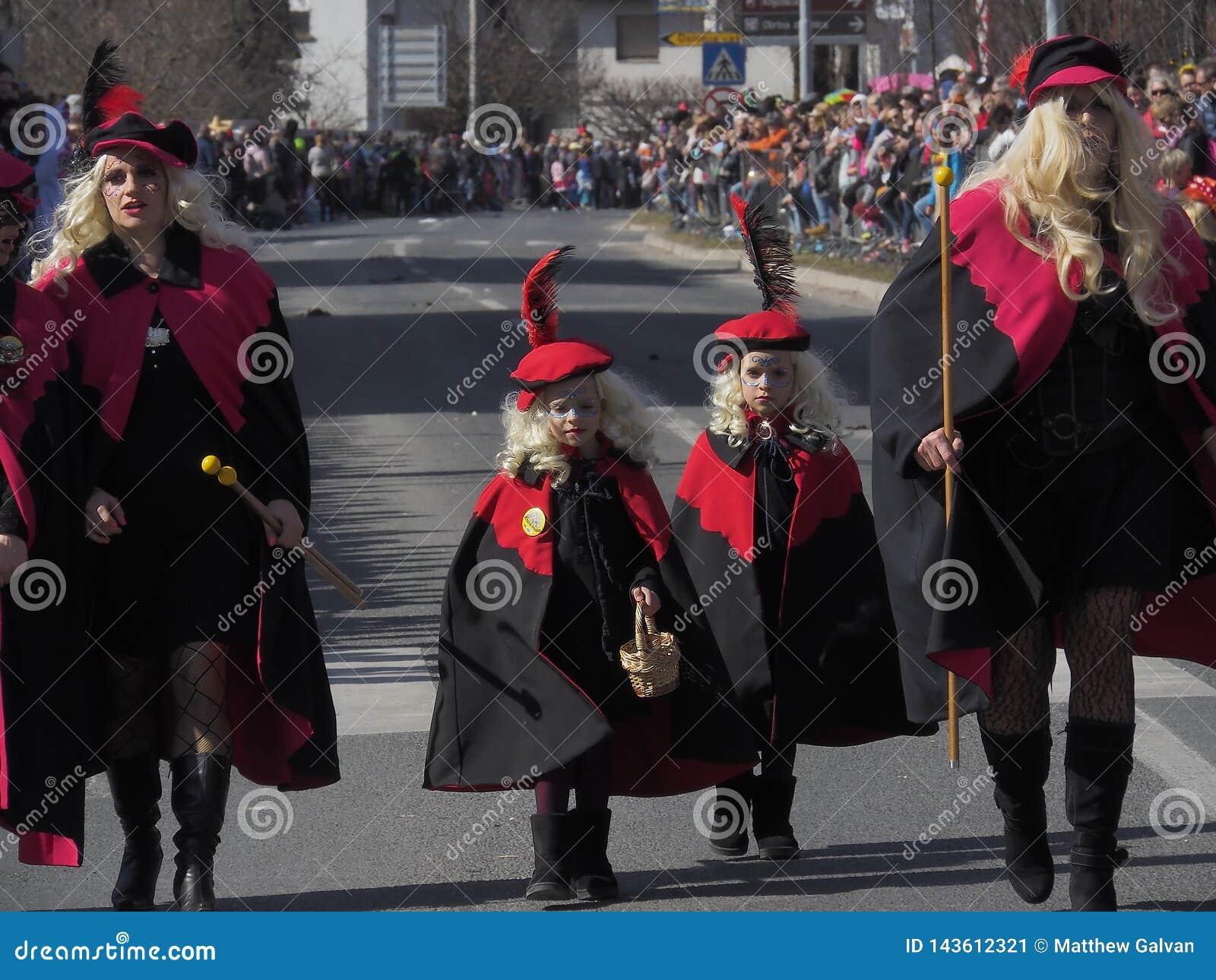 Mulheres e meninas nos trajes para a parada da mola