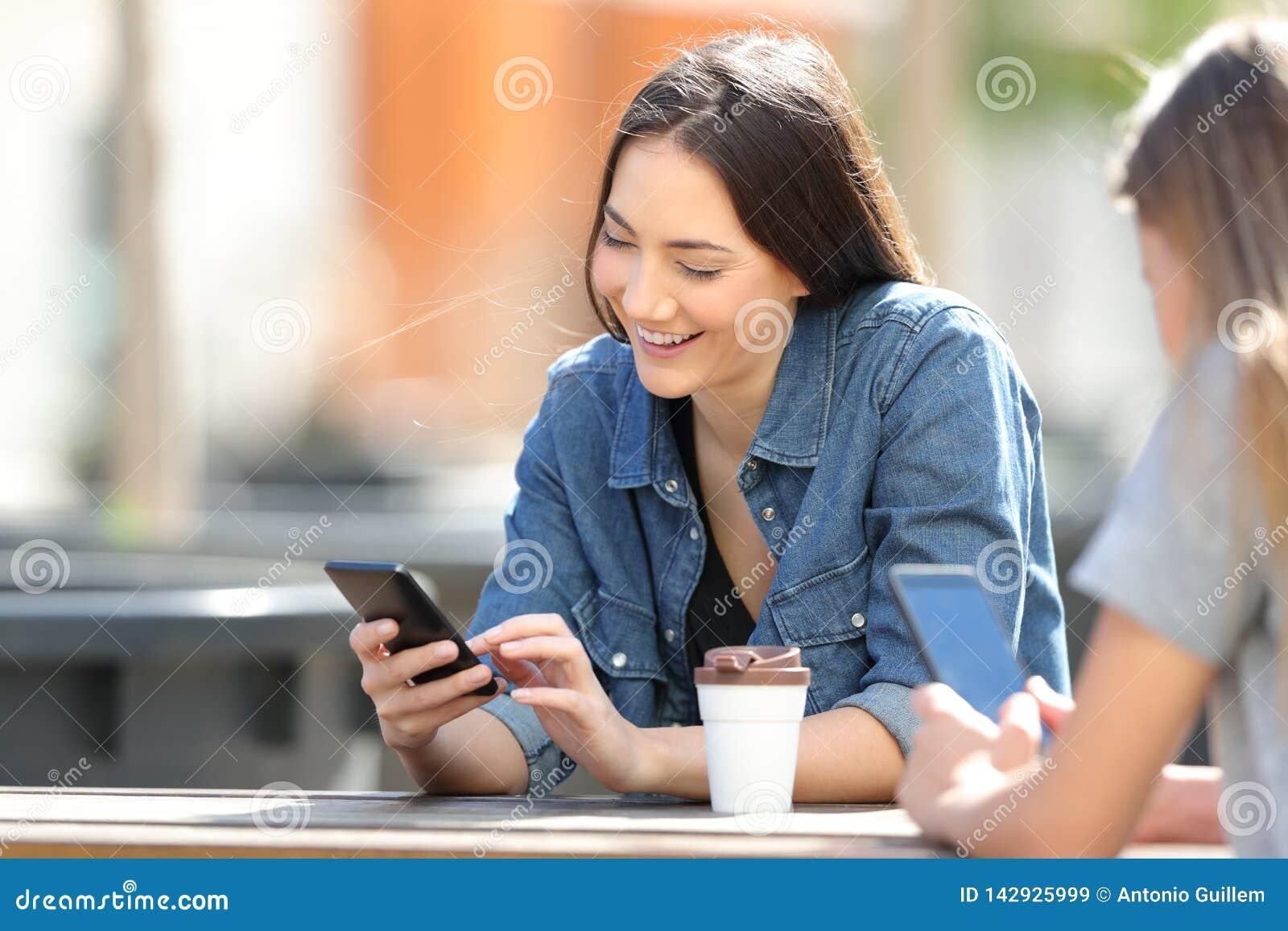 Mulheres felizes que usam telefones espertos em um parque