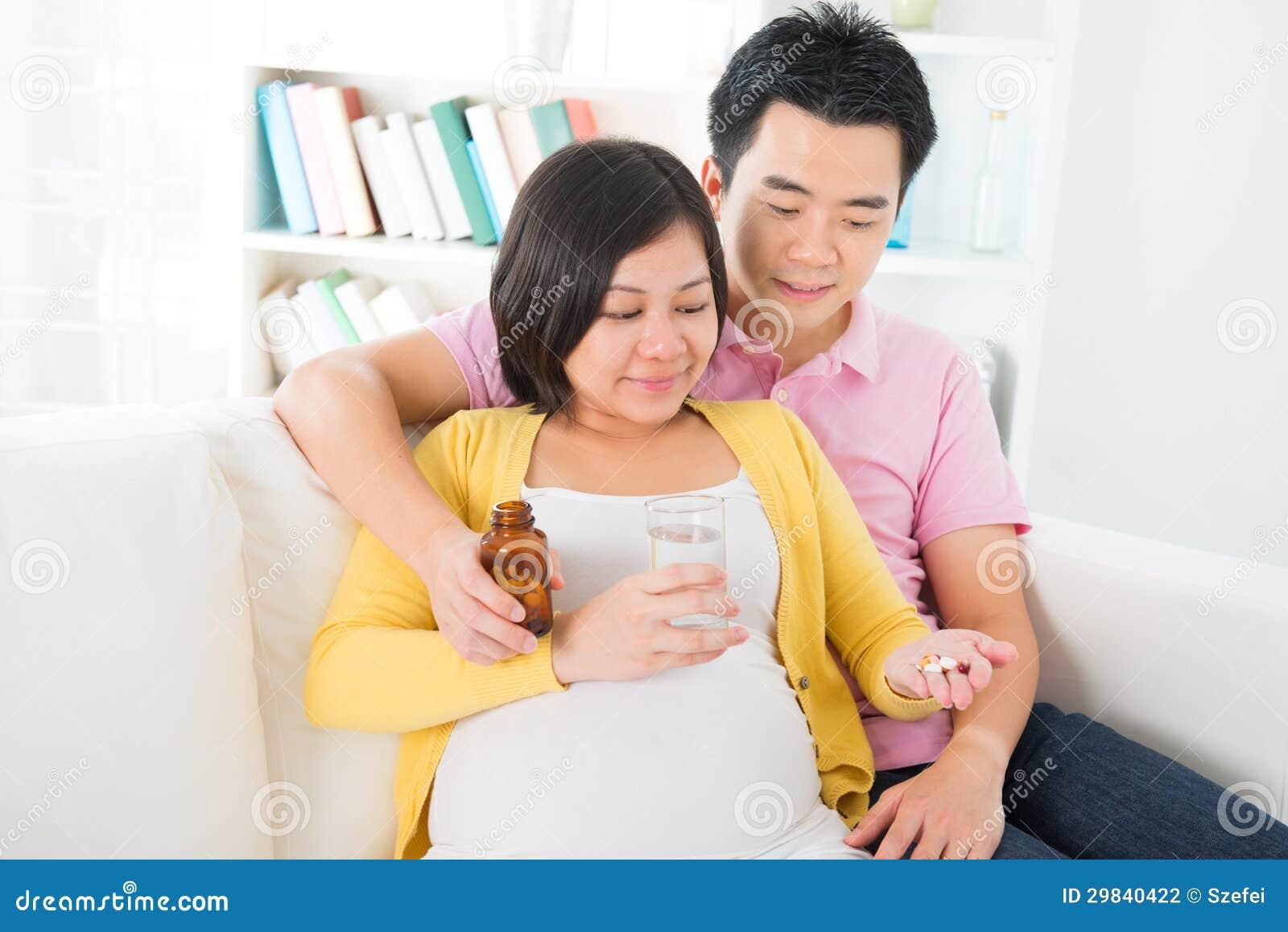 Mulher gravida asiática que tem a medicina em casa