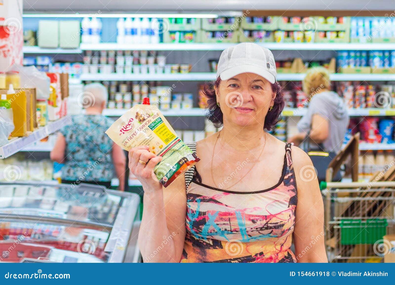 Mulheres maduras bonitas que mostram um bloco da maionese na mercearia