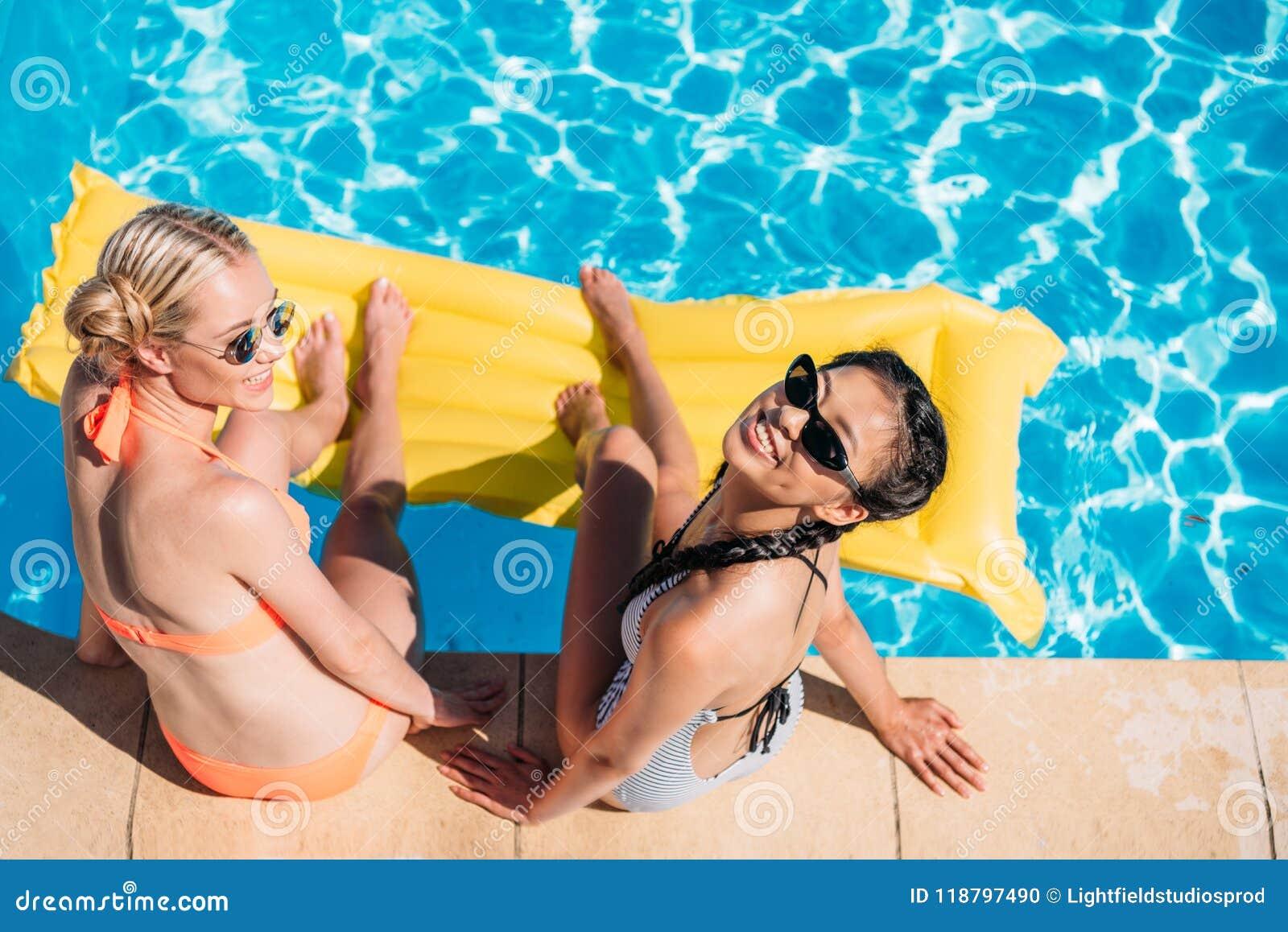 Mulheres multi-étnicos bonitas novas que sentam-se perto da piscina