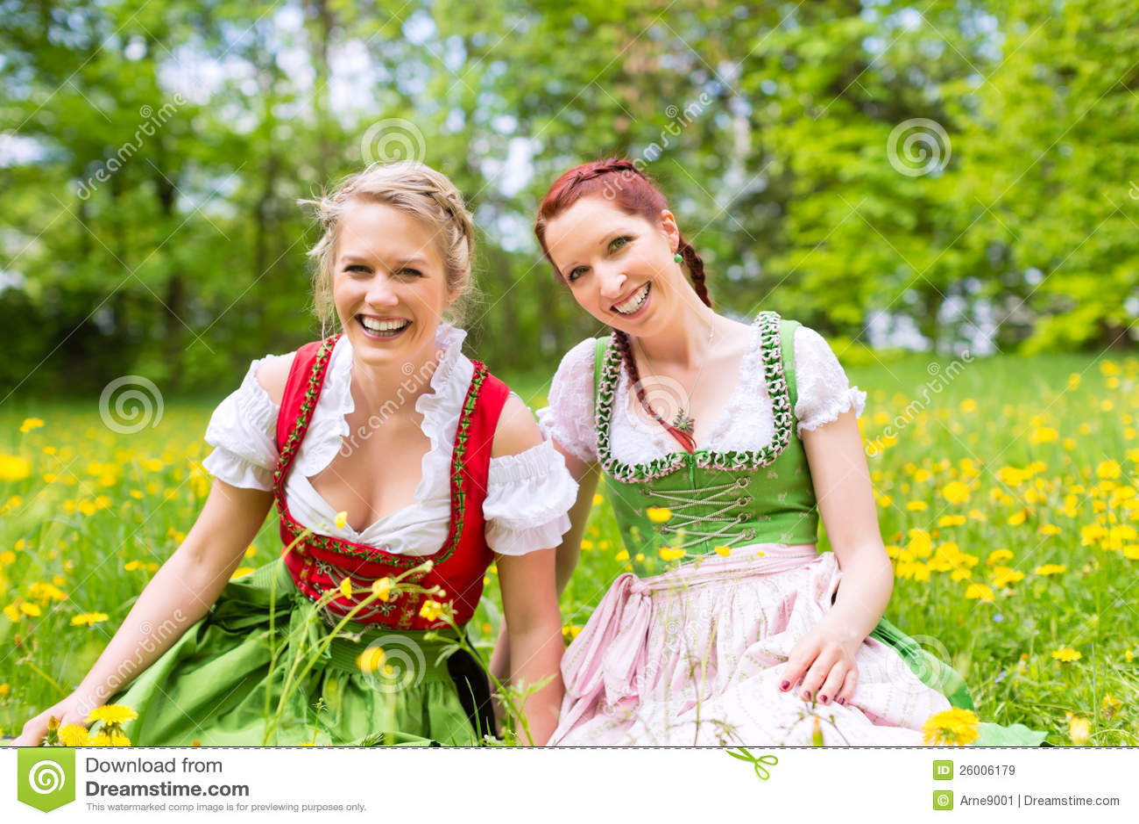 Mulheres na roupa ou no dirndl bávaro em um prado
