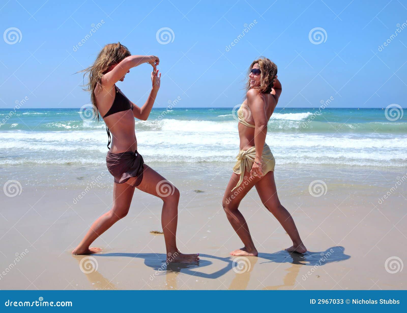 Mulheres novas na praia ensolarada