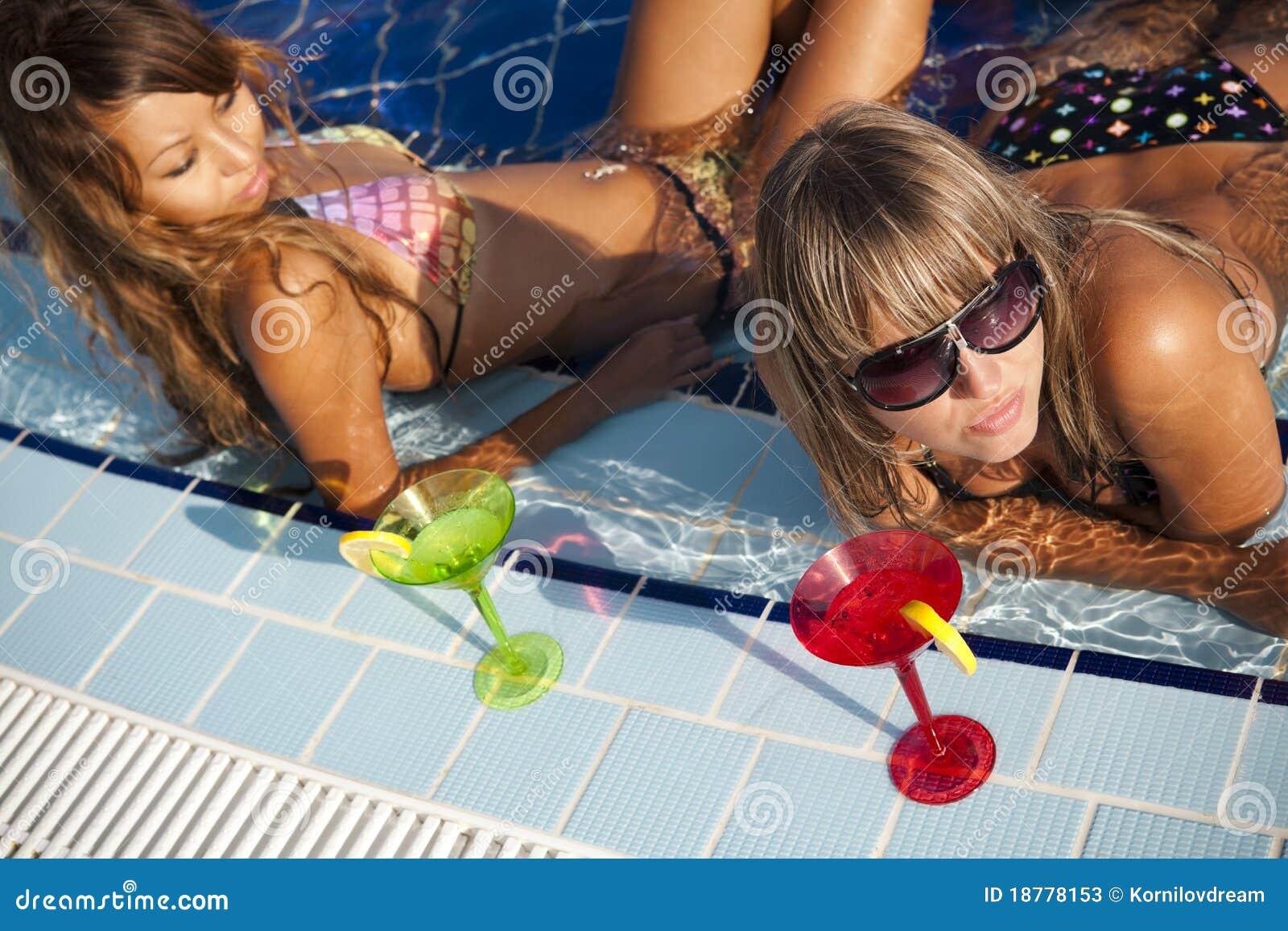Mulheres que apreciam na piscina