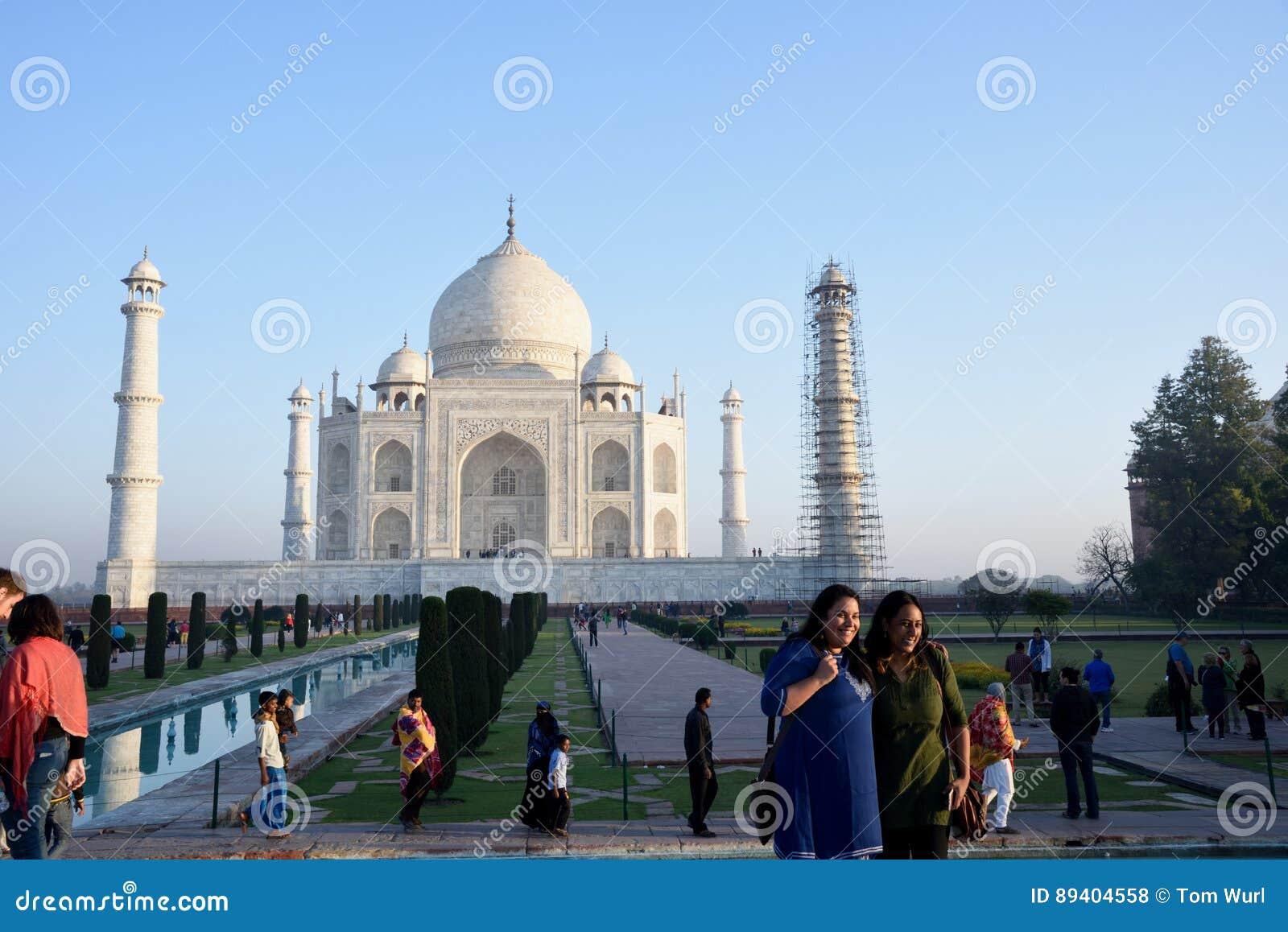 Mulheres que estão sendo fotografadas em Taj Mahal no amanhecer