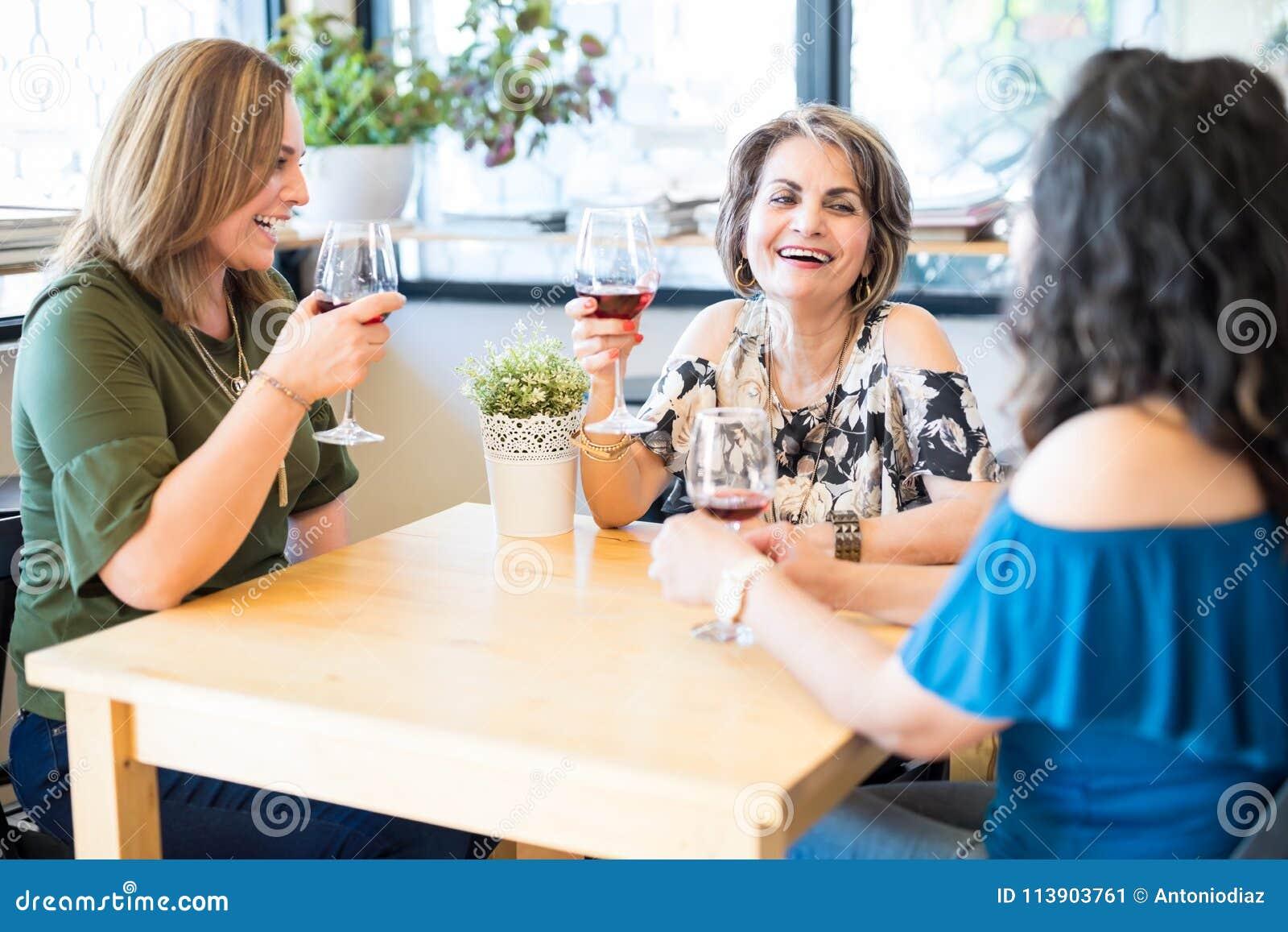 Mulheres que falam e que bebem o vinho no restaurante