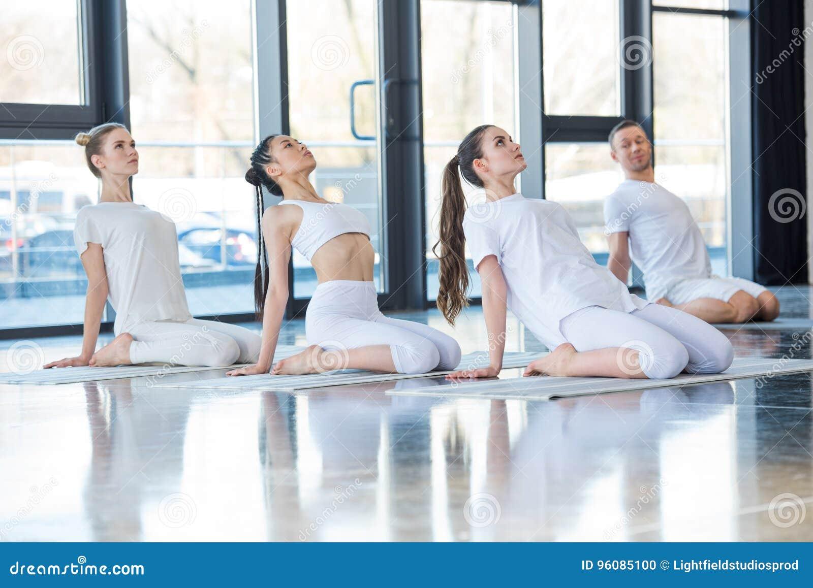 Mulheres que praticam a ioga em esteiras junto com o instrutor