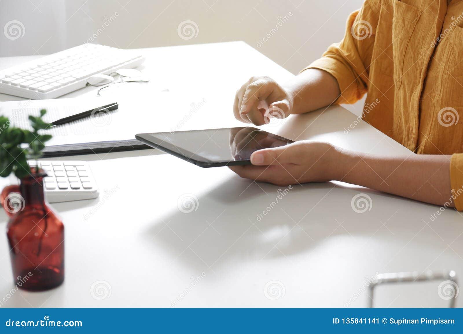Mulheres que usam a tabuleta ao trabalhar em seu escritório
