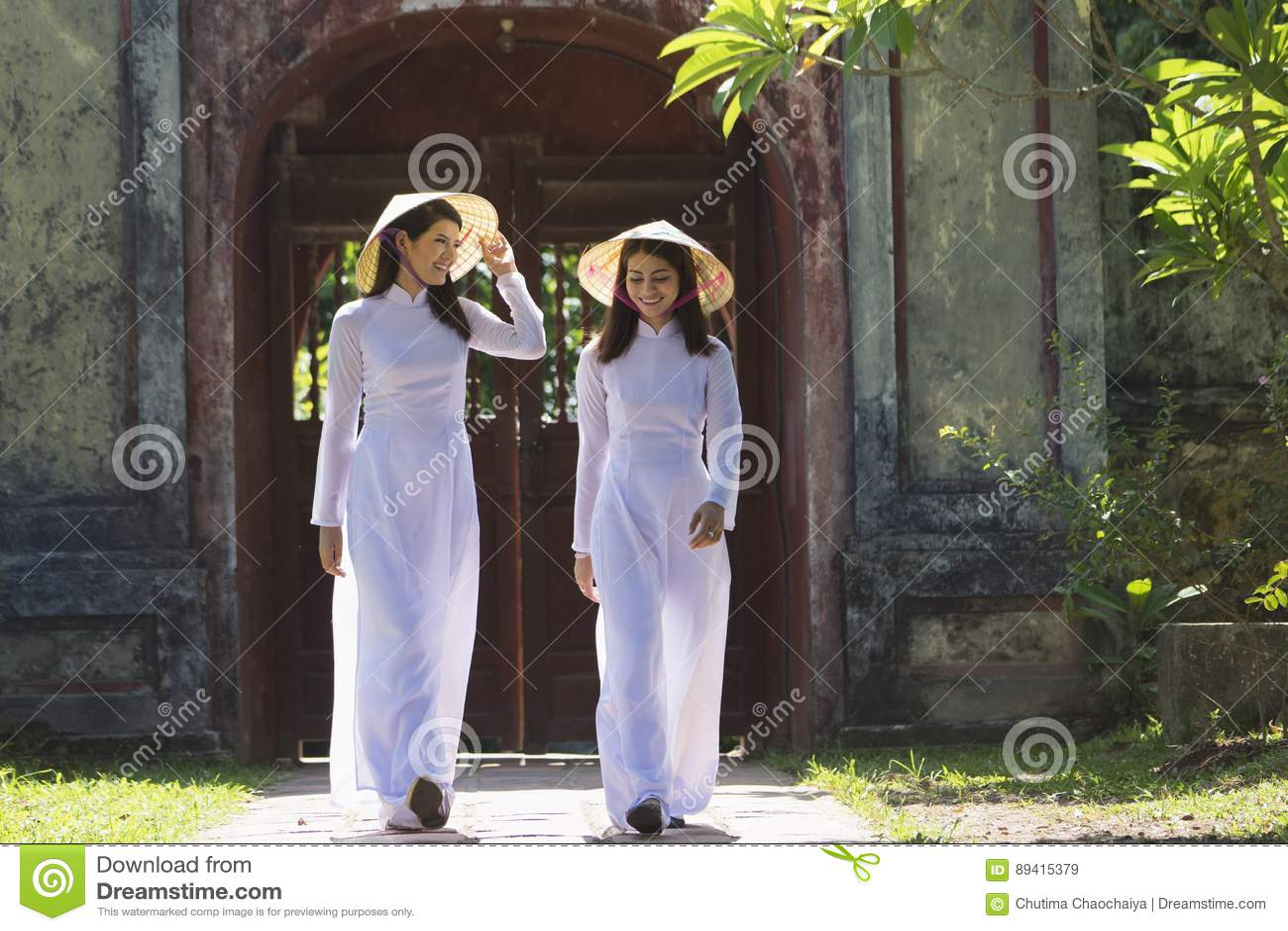 Mulheres vietnamianas que vestem o terno tradicional que anda no templo