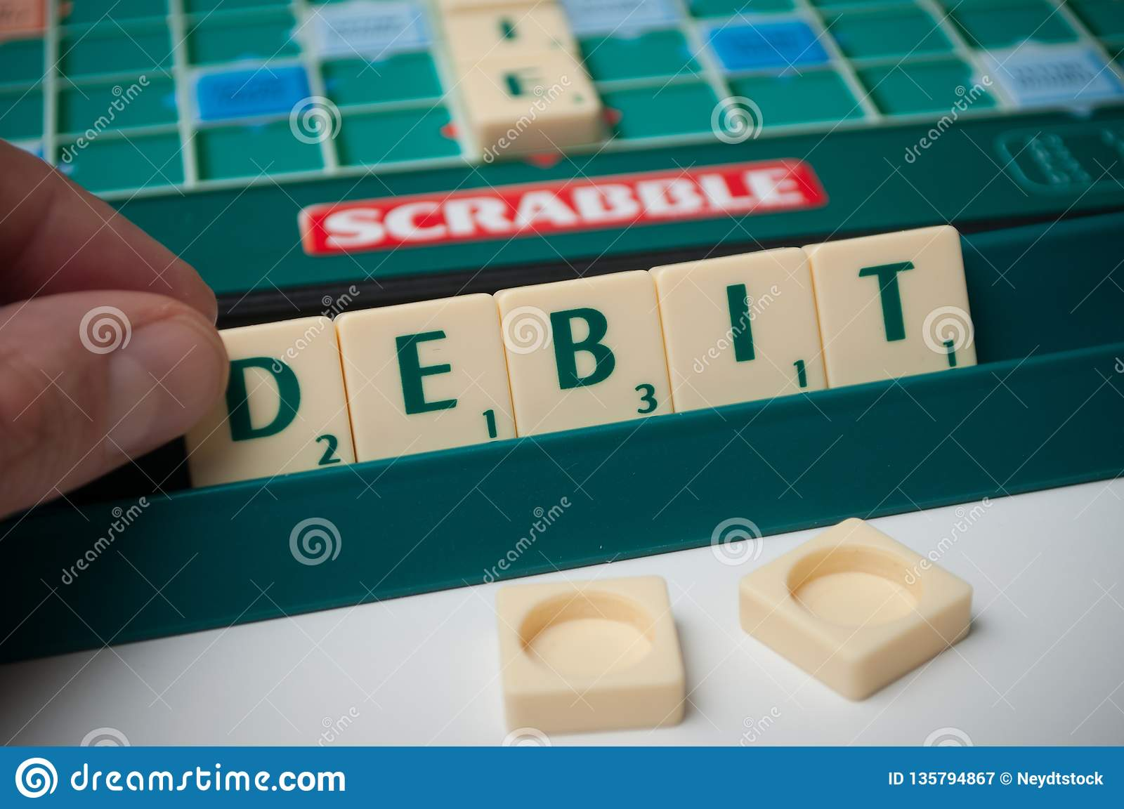 Plastic Letters On Scrabble Board Game With Word : Debit