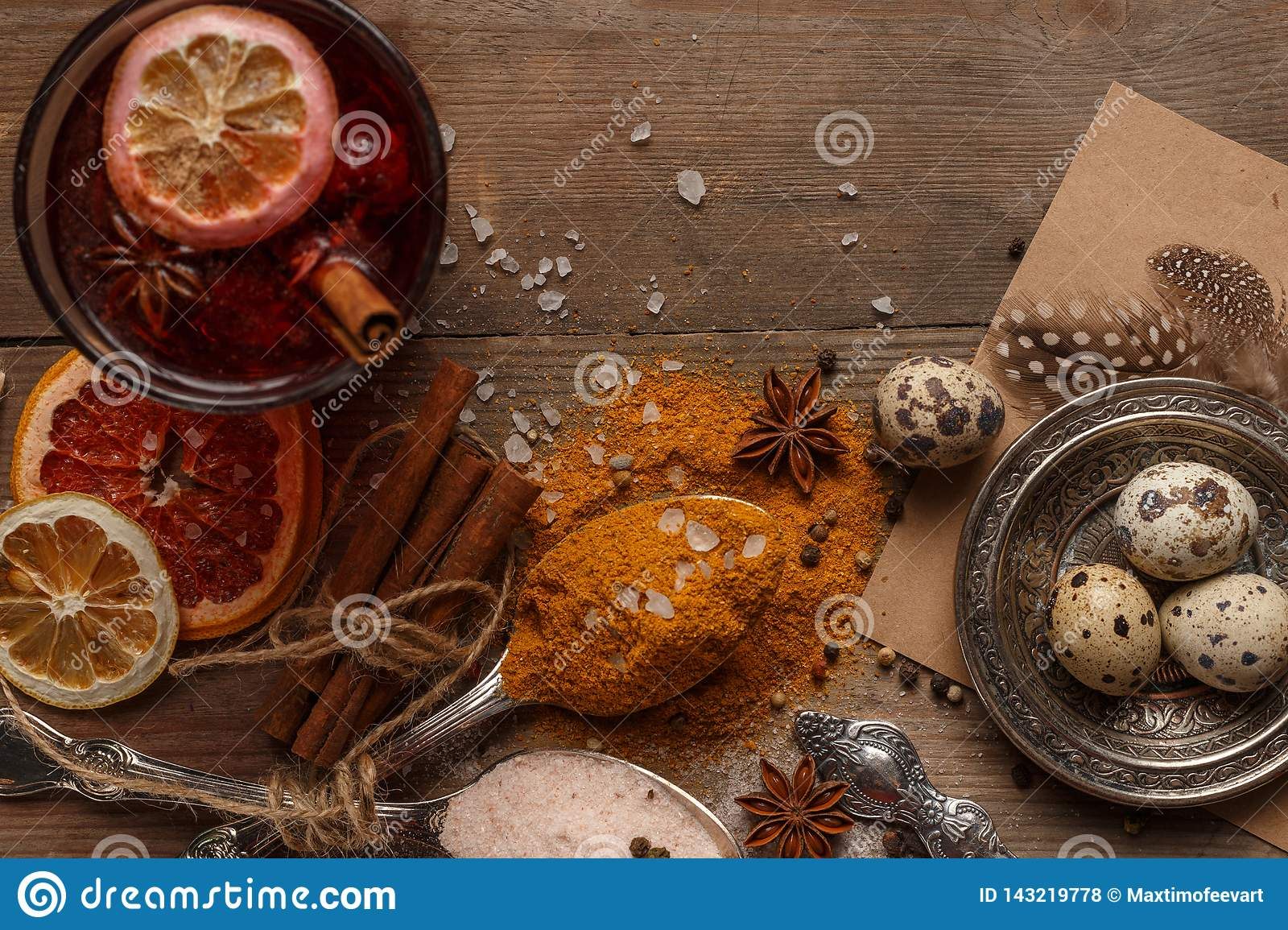 Mulled wine, spices and dried fruits on a rustic table