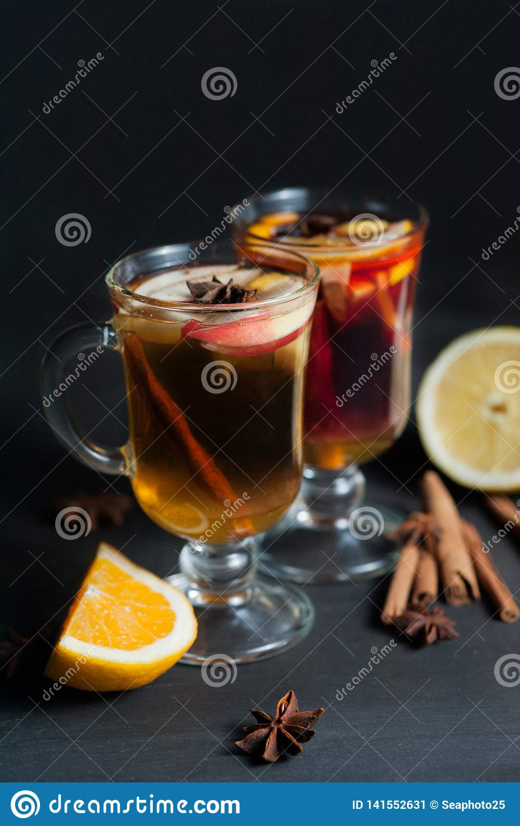 Mulled wine in white rustic mugs with spices and citrus fruits