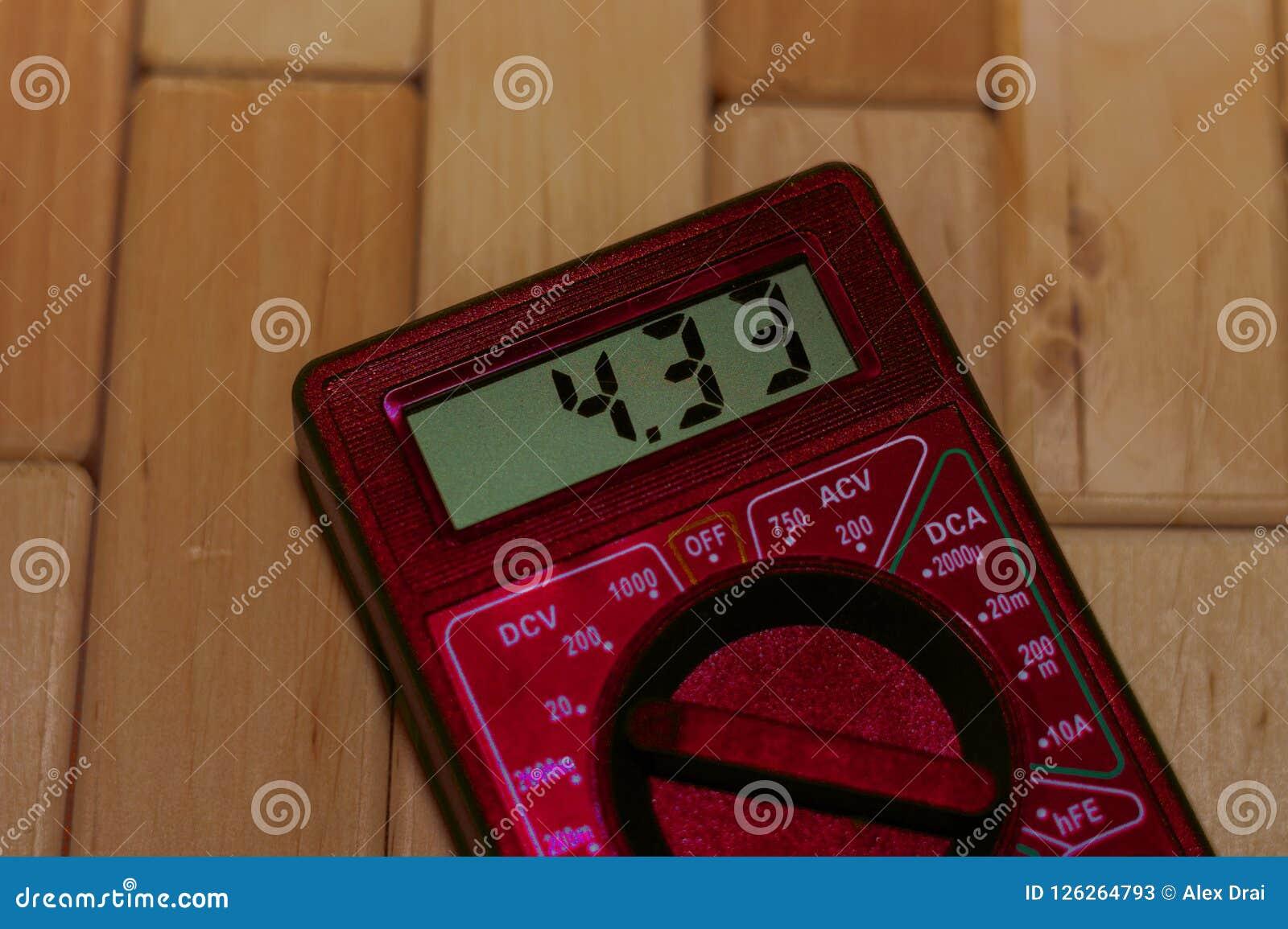 Multímetro de medição digital vermelho no assoalho de madeira Mostra 4 33V ou bateria inteiramente carregada Inclui o voltímetro,