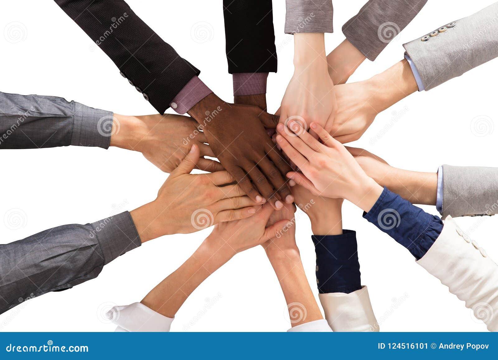 Multi этнические бизнесмены штабелируя руки