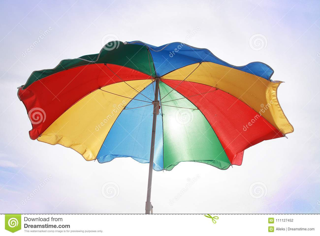 9921a0005 Multi-colored beach umbrella against the background of a light sky. For  summer season.