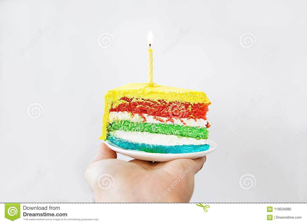Multi Colored Birthday Cake With One Candle On A Light Background