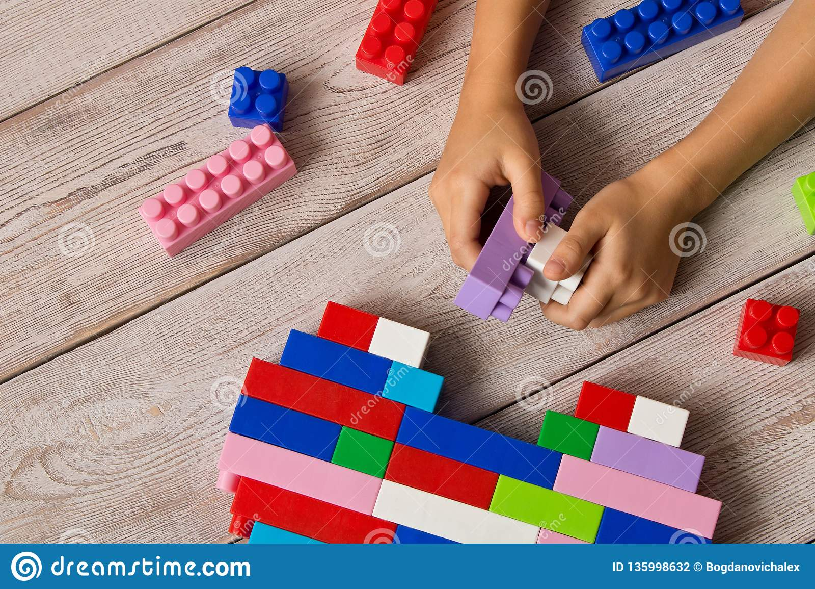 Multi-colored plastic aannemer in de handen van het meisje Kinderen` s onderwijsspelen