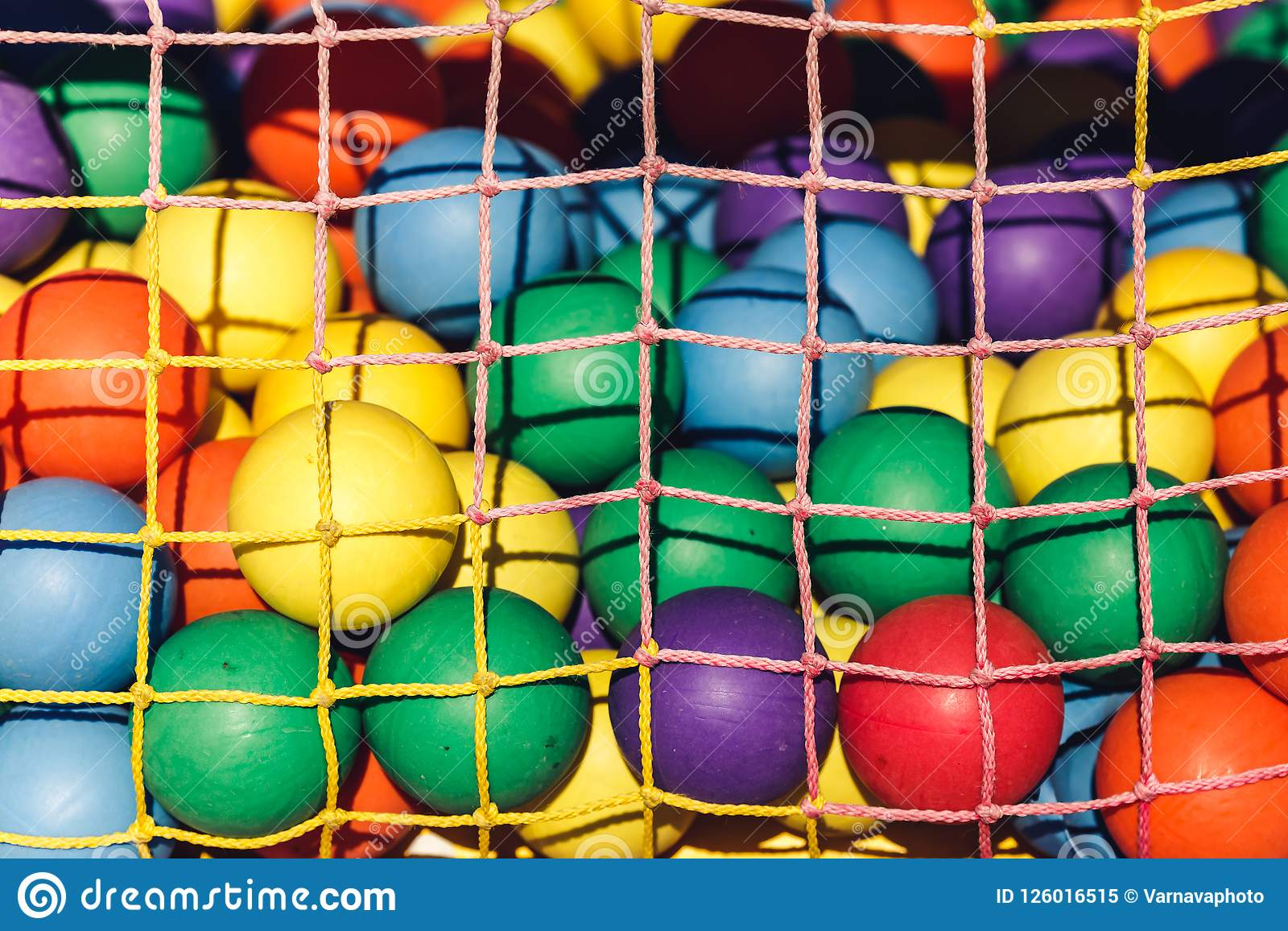 Multi-colored plastic balls for children`s maze behind grid.