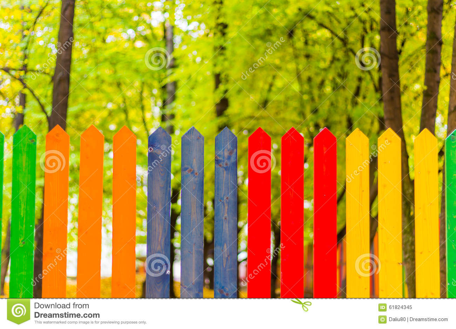 Multi colored rainbow wooden fence in autumn garden