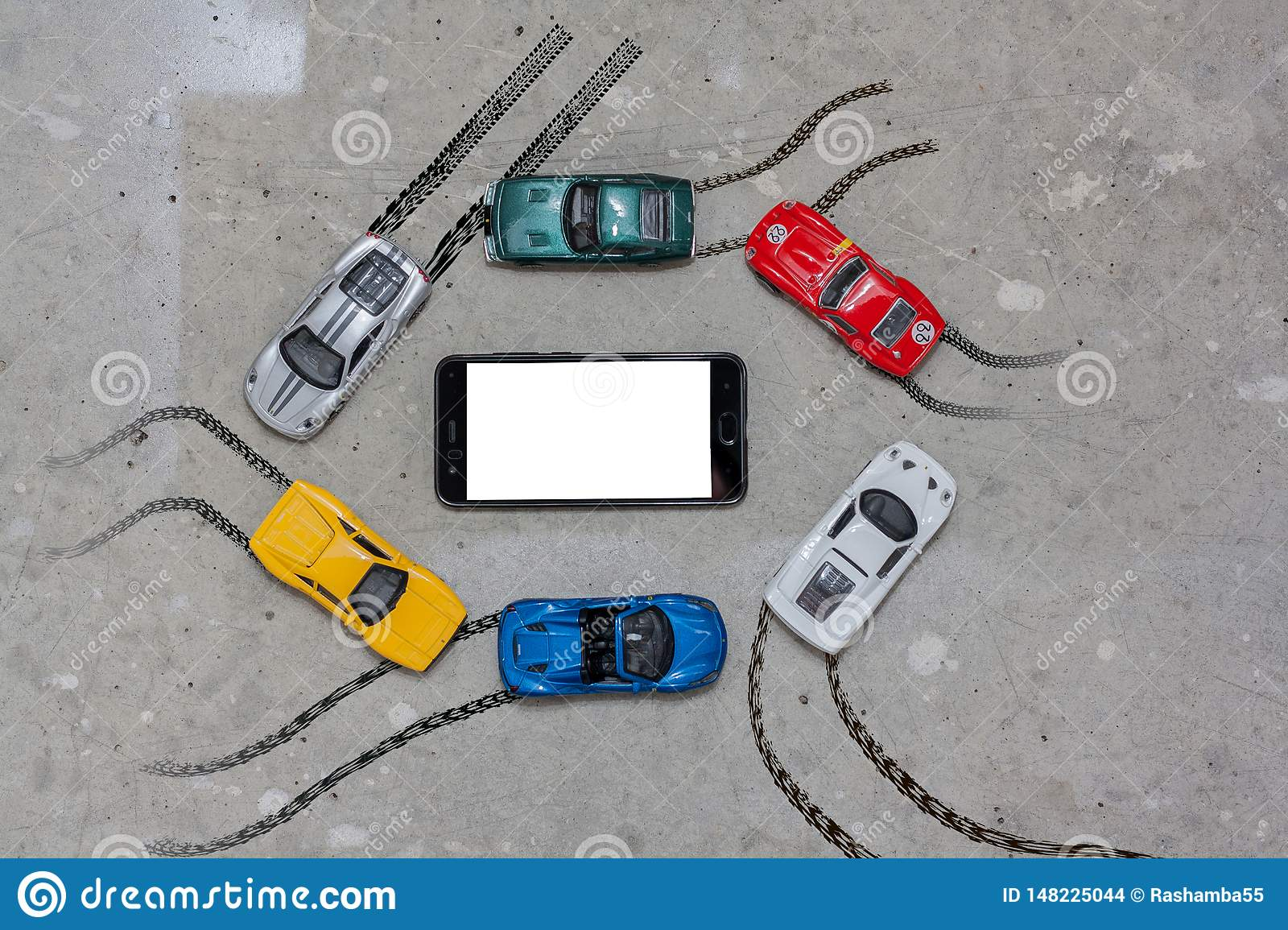Toy cars multi colored around a mobile phone top view
