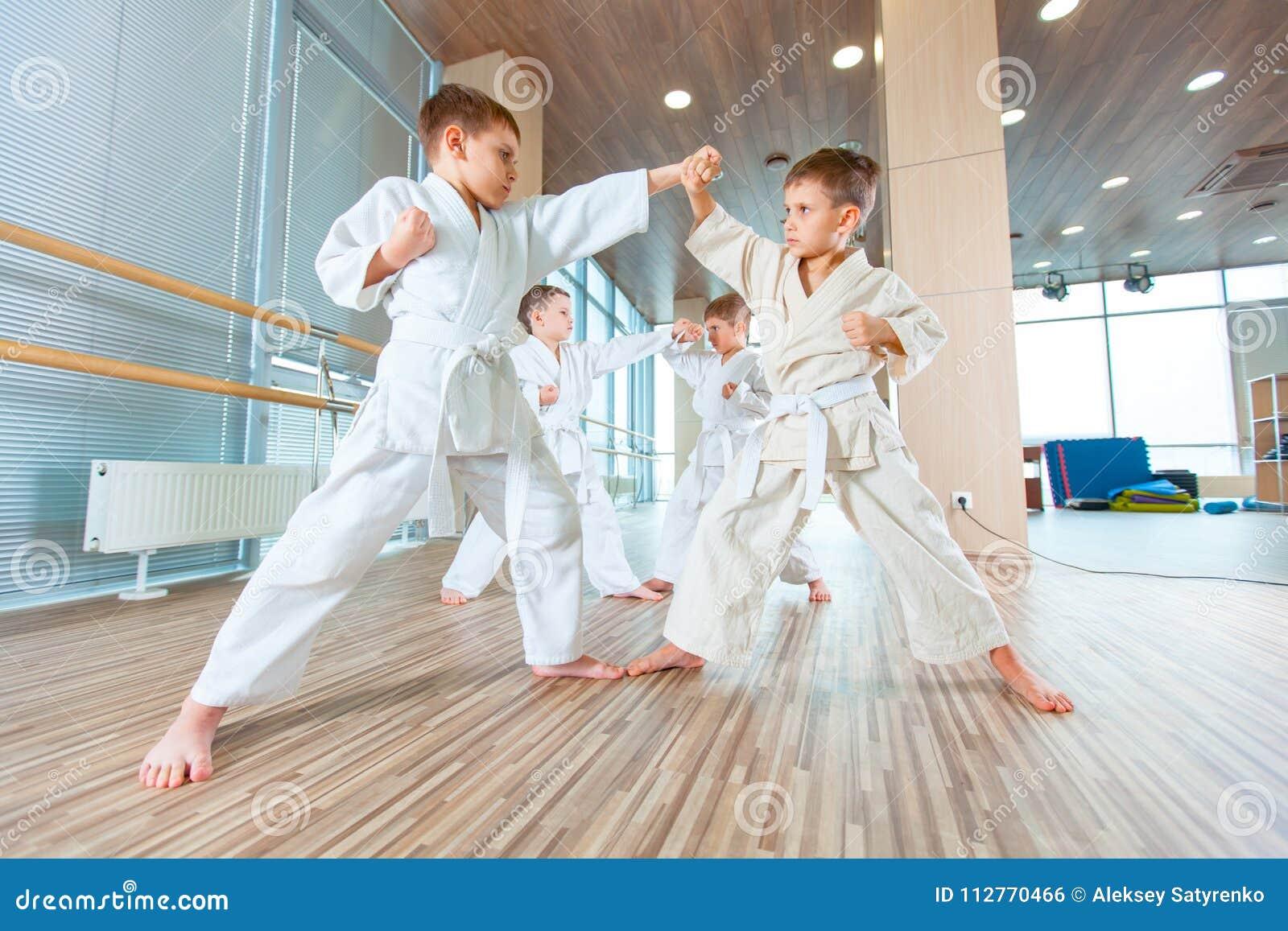 Multi crianças éticas novas, bonitas, bem sucedidas na posição do karaté